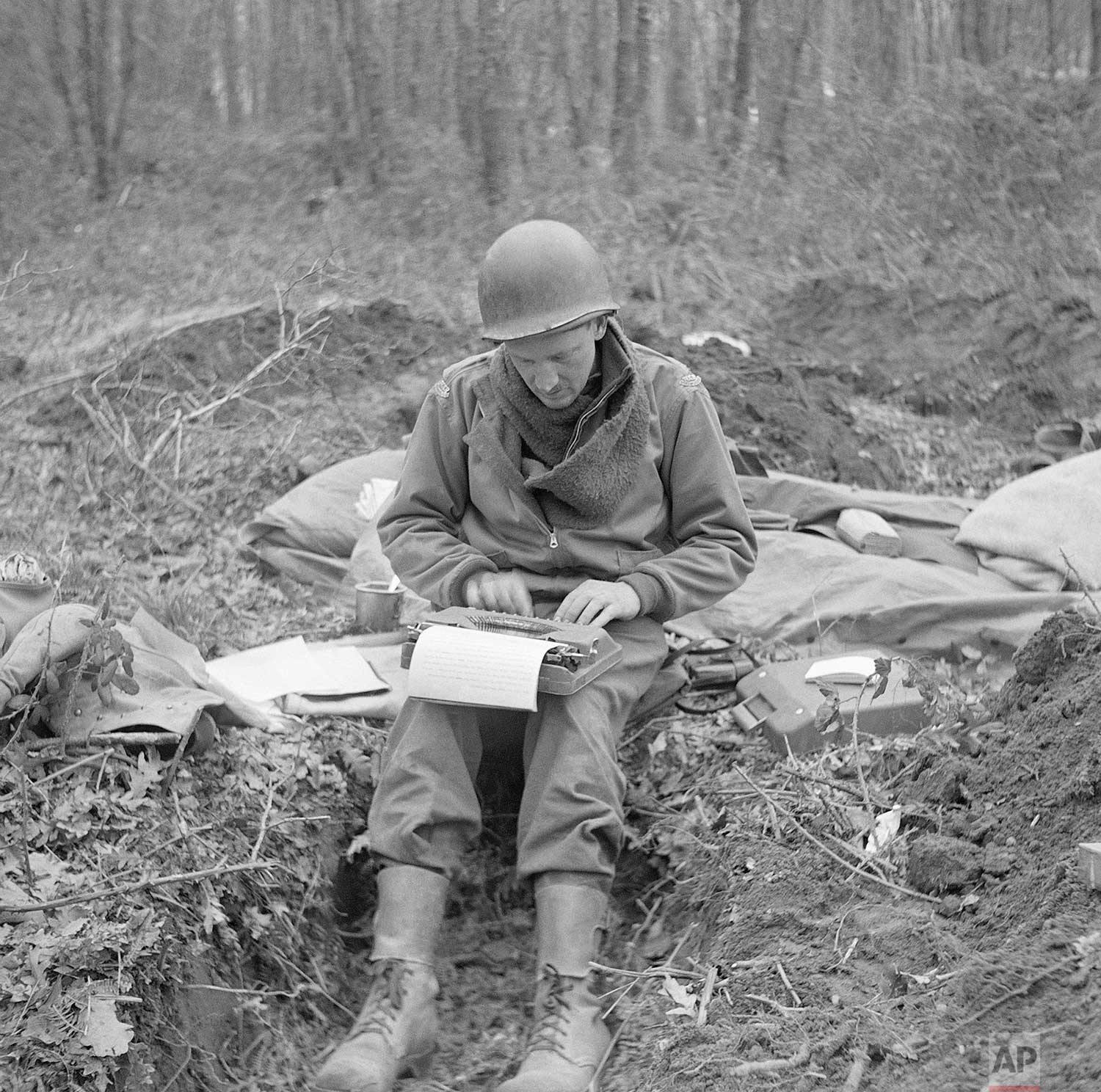 Don Whitehead, Associated Press correspondent, writes his story of the landing at Anzio Beach in Italy, from a fox hole in February 1944. (AP Photo/Bill Allen)