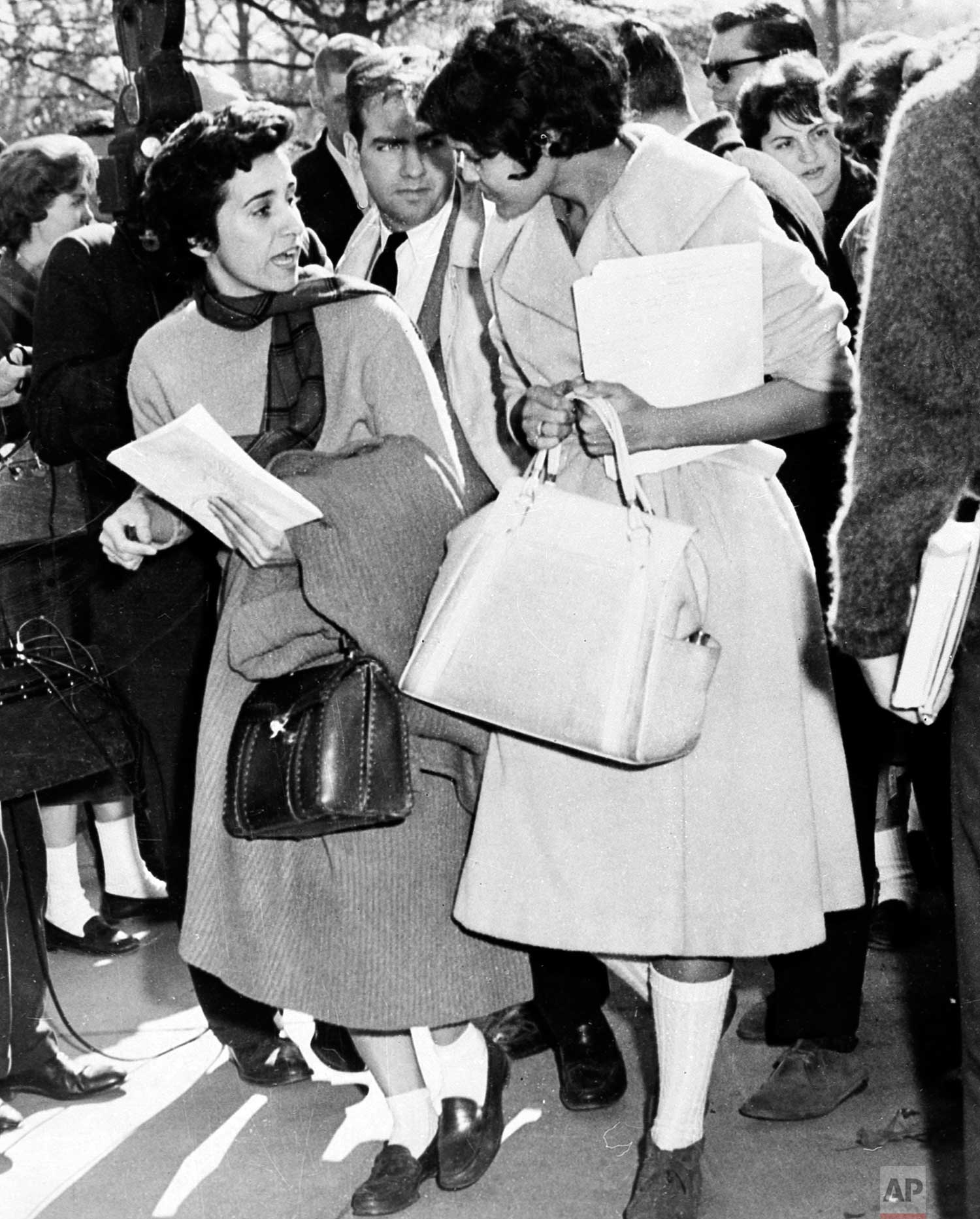 """Atlanta Associated Press staffer Kathryn Johnson, left, donned bobby socks and a sweater to obtain the only eyewitness story of Charlayne Hunter's first day of class at the University of Georgia, Jan. 11, 1961. School officials stopped all other reporters at the door but Kathryn was """"just another student."""" Hunter was one of the first two African American students to enroll in the University of Georgia. (AP Photo)"""