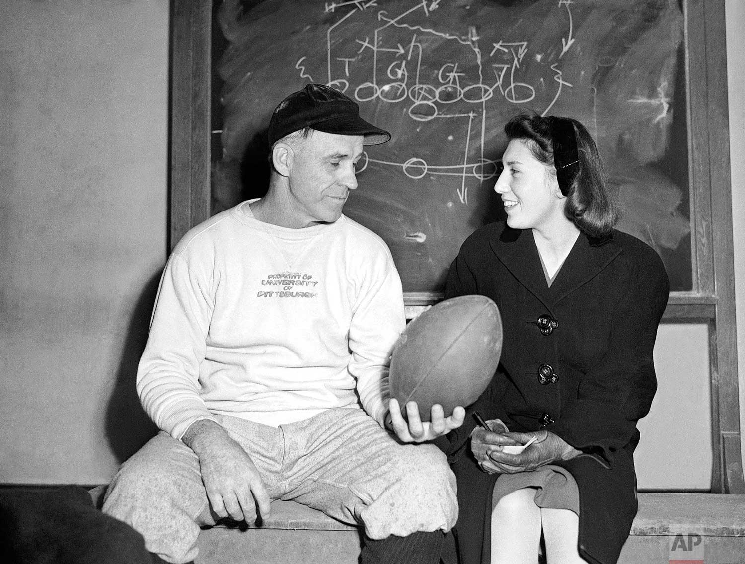 Elaine Kahn, Pittsburgh AP staffer, talks with Clark Shaughnessy, University of Pittsburgh gridiron coach, about 1946 prospects in Pittsburgh, January 1946. (AP Photo/Walter Stein)