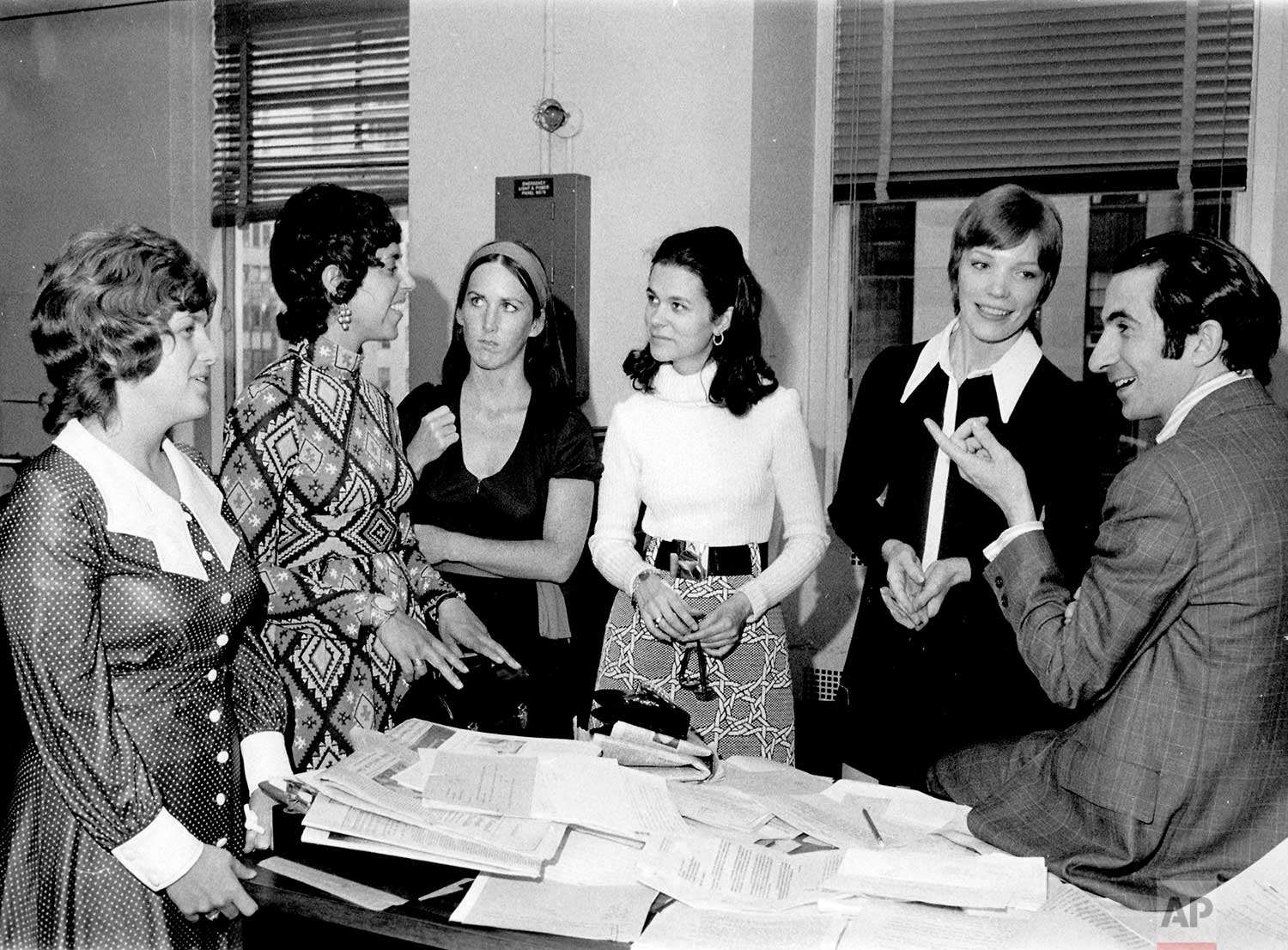 """AP newswomen were briefed by AP Managing Editor Lou Boccardi, during an orientation visit to the AP General Office in New York. AP World, the employee magazine, will announce in its next issue that the term """"newswoman"""" will be used in the future to describe women reporters. Heretofore male and female writers all were classified as """"newsman."""" From left: Jackie Snyder, Pittsburgh bureau; Debby Rankin, Chicago; Janet Bataile, Des Moines; Mary Gordon, Newark, Nancy Shipley, Nashville and Bocccardi, 1971. (AP Photo/Corporate Archives)"""