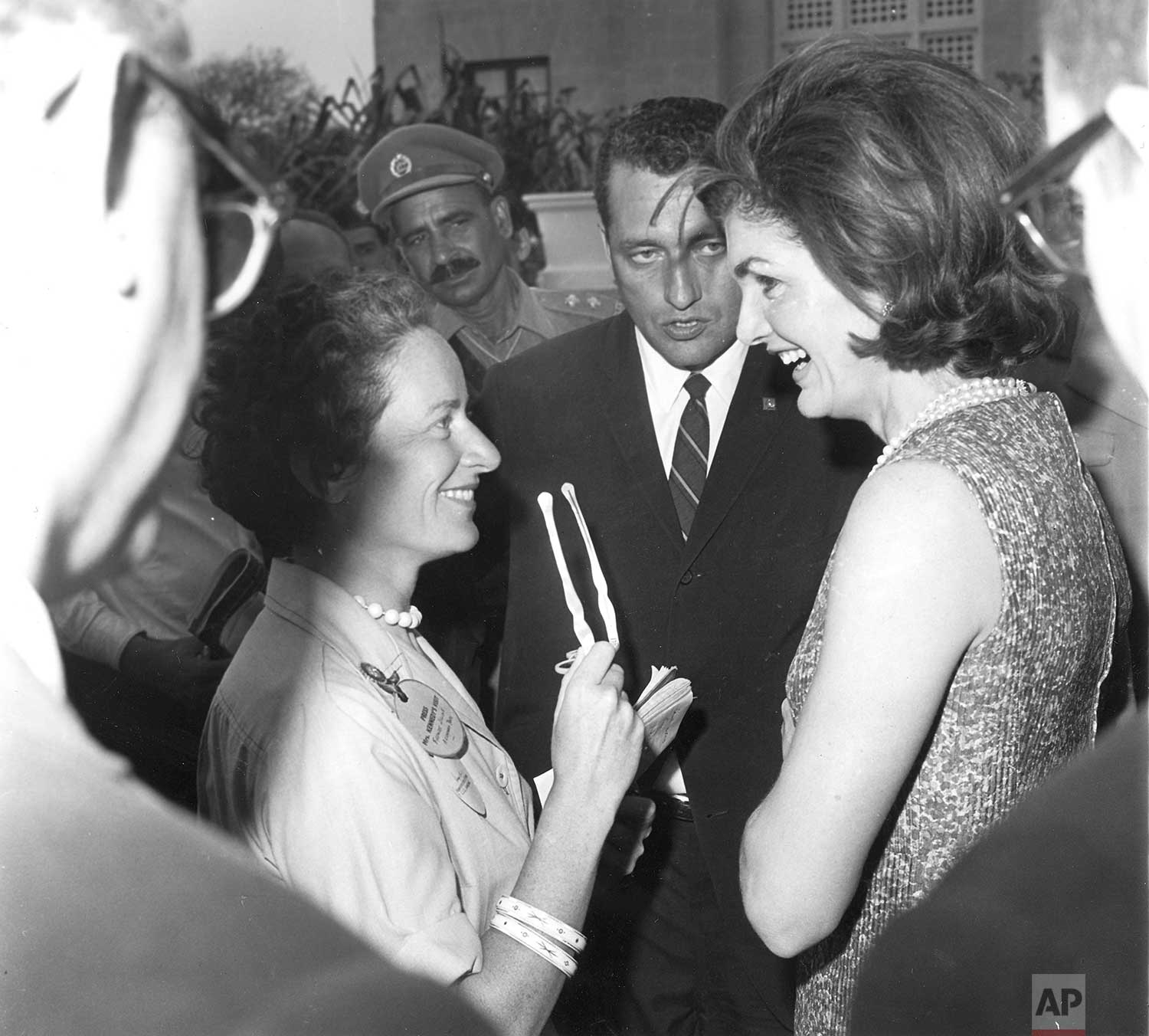 Frances Lewine, left, of The Associated Press talks with Mrs. Jaqueline Kennedy on the lawn of the Governor's residence at Karachi, Pakistan, after the First Lady had dismounted from a camel ride. Miss Lewine was a member of the press contingent that covered Mrs. Kennedy's world tour in March 1962. (AP Photo/Corporate Archives)