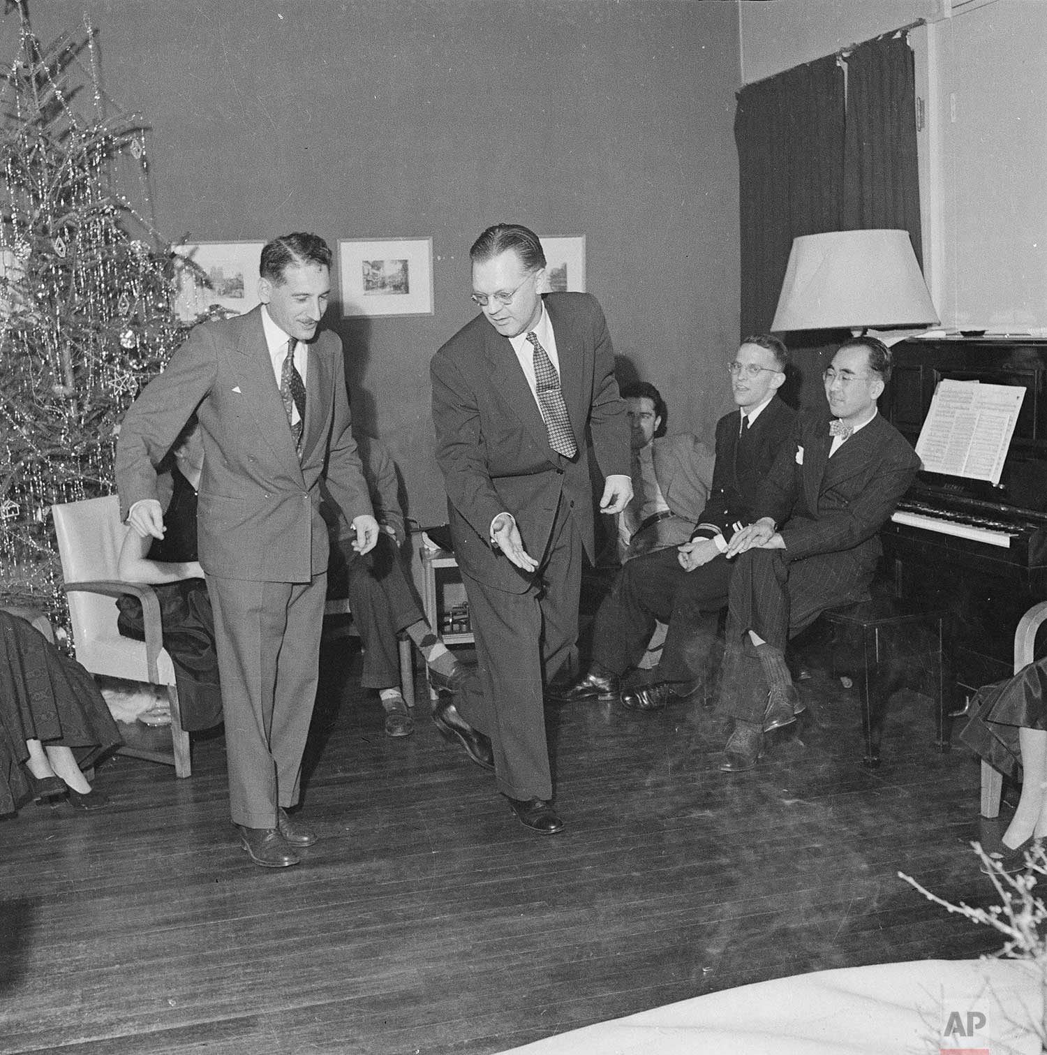 The Tokyo bureau staff enjoyed a Christmas party at Chief of Bureau Bob Eunson's house.  The smooth dance team tapping out a hot waltz clog is photographer Max Desfor and bureau chief Bob Eunson, 1951. (AP Photo)