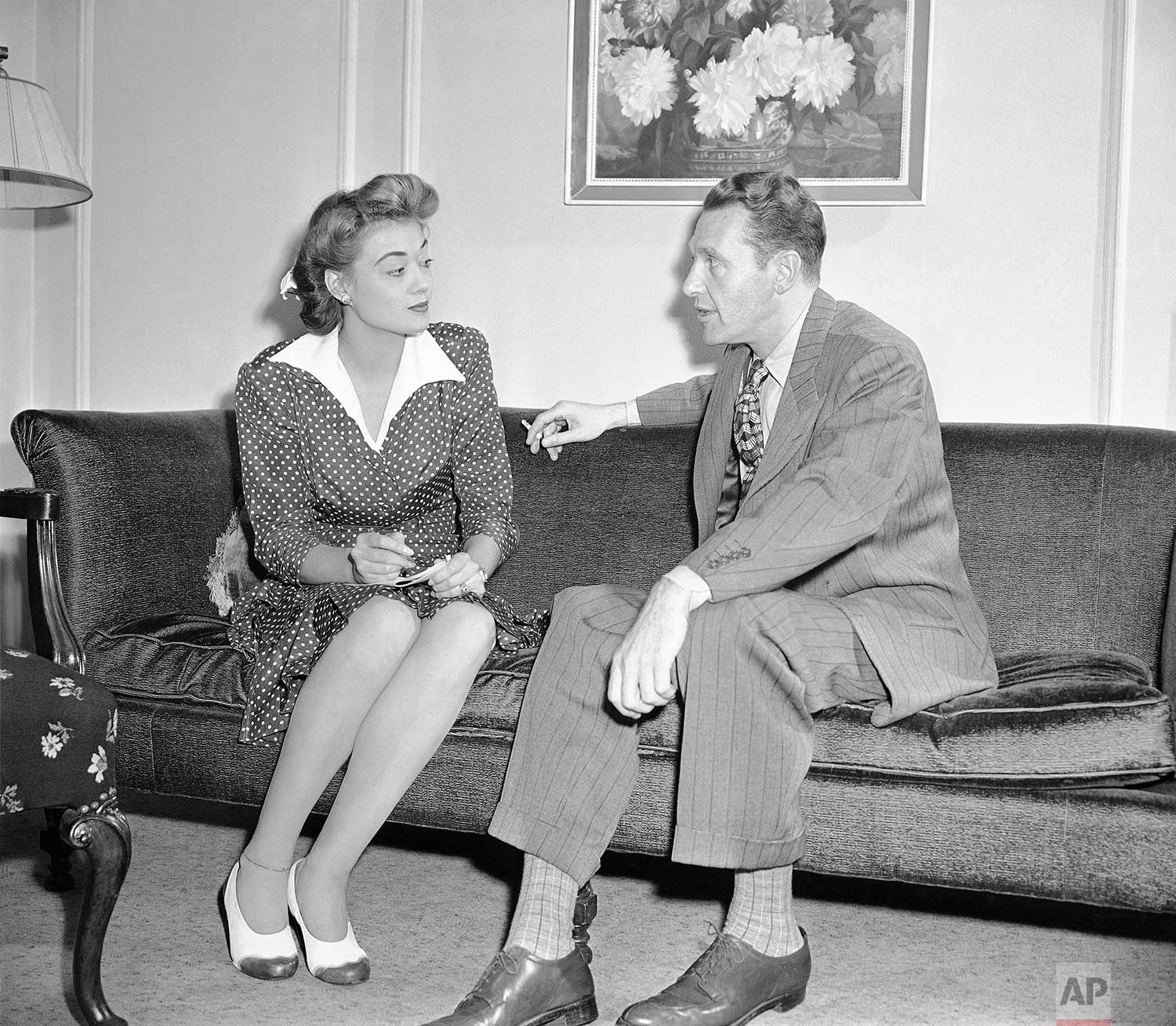 """Actor Ralph Bellamy has appeared in 83 movies, but he's deserted Hollywood temporarily to play a smash role in a current Broadway hit, """"Tomorrow, The World."""" Miss Frances Long, Associated Press reporter, interviews Mr. Bellamy in his New York apartment, July 23, 1943. (AP Photo/Charles Kenneth Lucas)"""