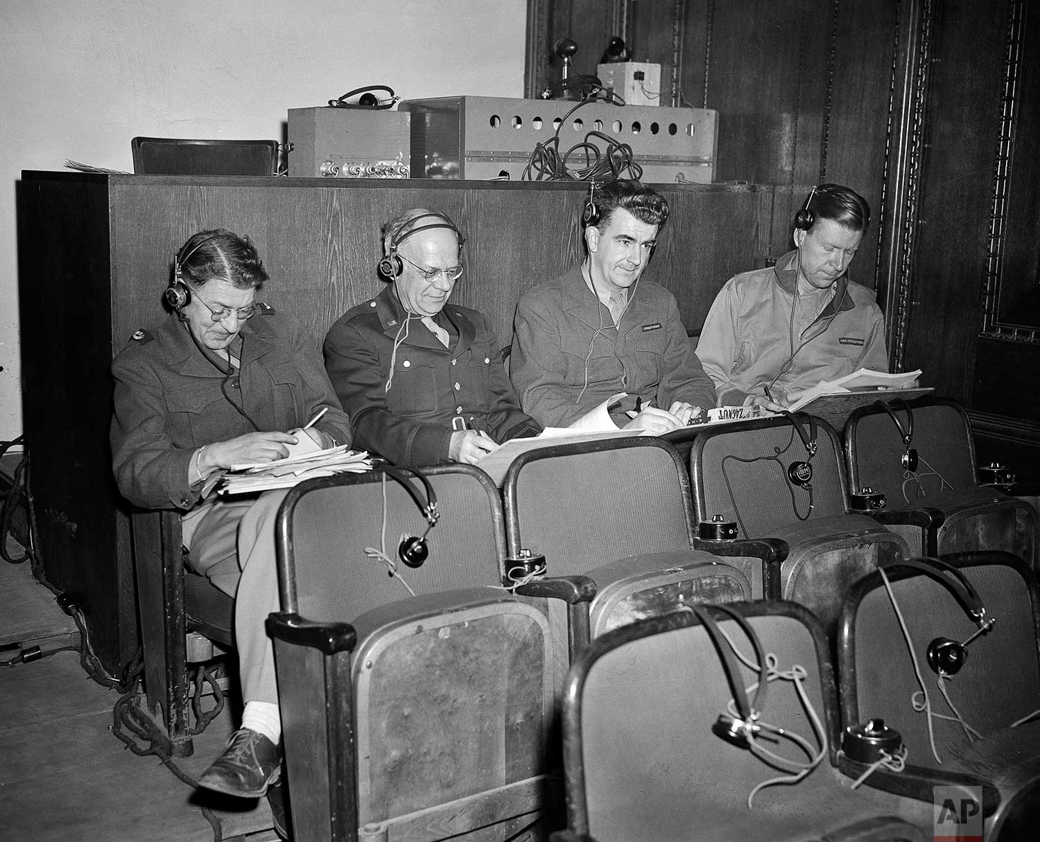 Four staff writers for The Associated Press are pictured working in the courtroom where the Nuremberg war crimes trials are being held, December 1945. From left: Boots Norgaard, Louis Lochner, Wes Gallagher and Dan DeLuce. (AP Photo/B.I. Sanders)