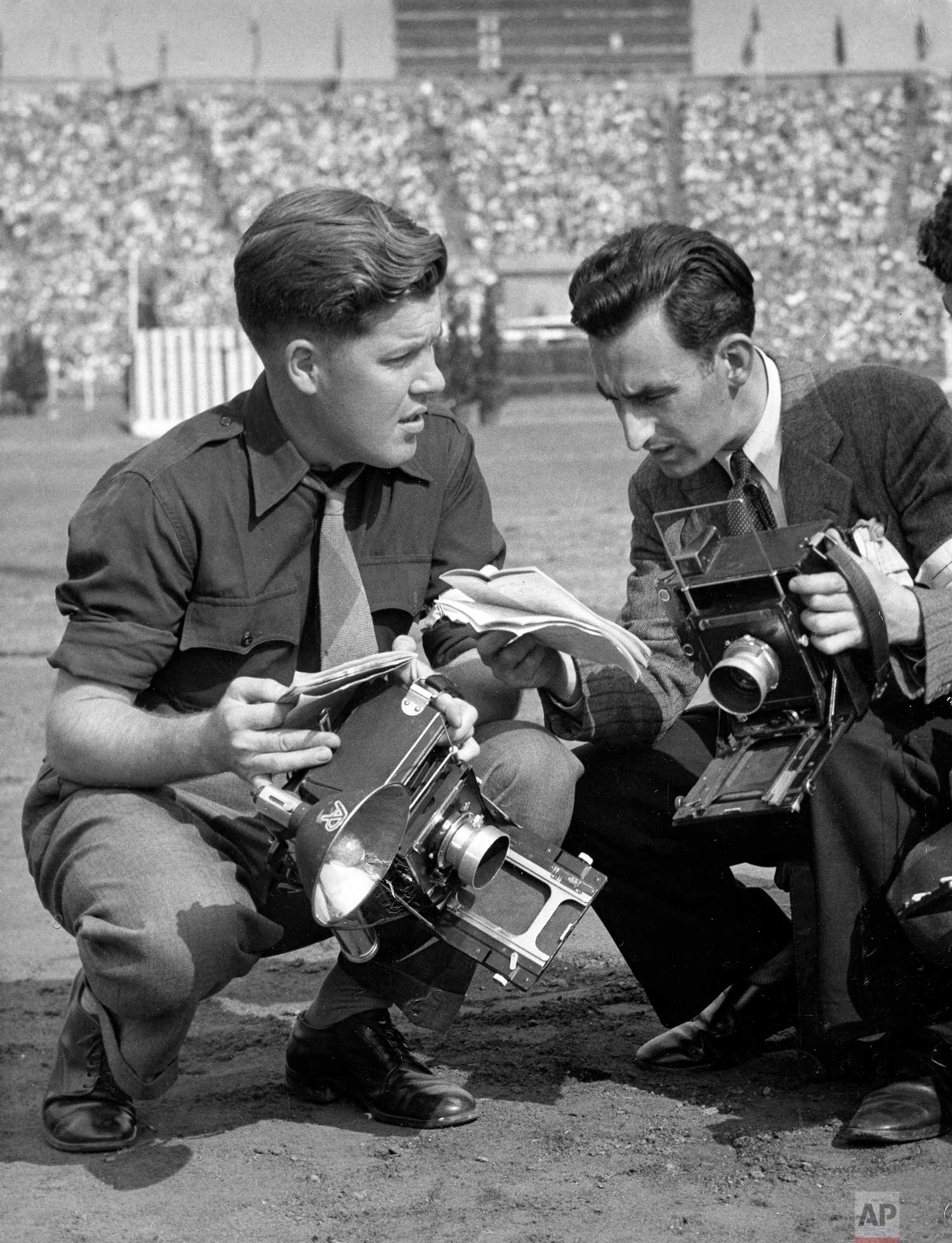 AP Boston photographer J. Walter Green, assigned to Rome, discusses coverage with AP London photographer Lawrence Harris at London's Wembley Stadium during the Summer Olympics, August 1948. (AP Photo)