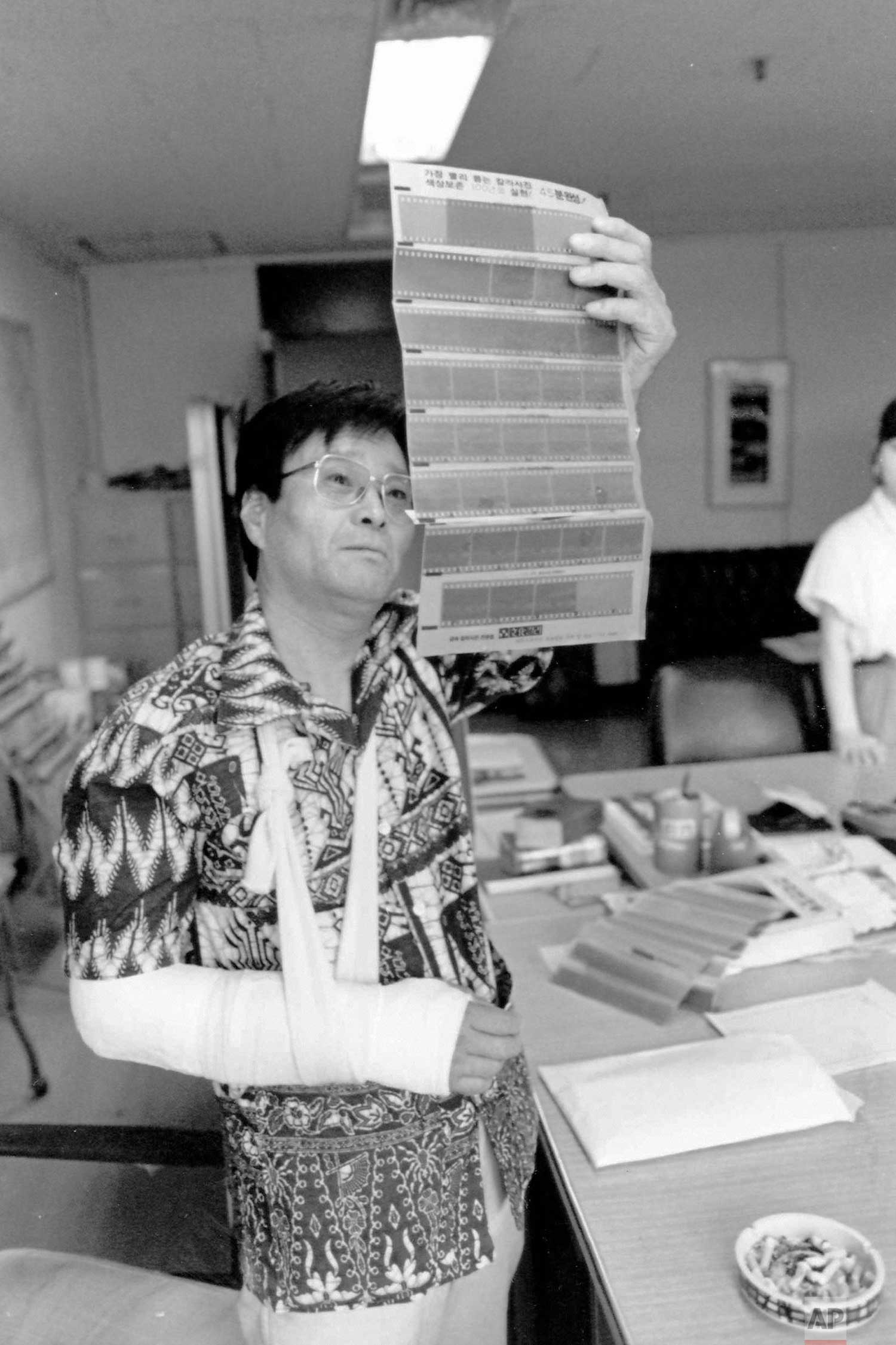 In this circa 1987 photo, AP photographer Kim Chon-kil looks at negatives at the Seoul, South Korea bureau. Kim suffered a broken arm when he was caught between rock-throwing students and riot police. (AP Photo/Corporate Archives)