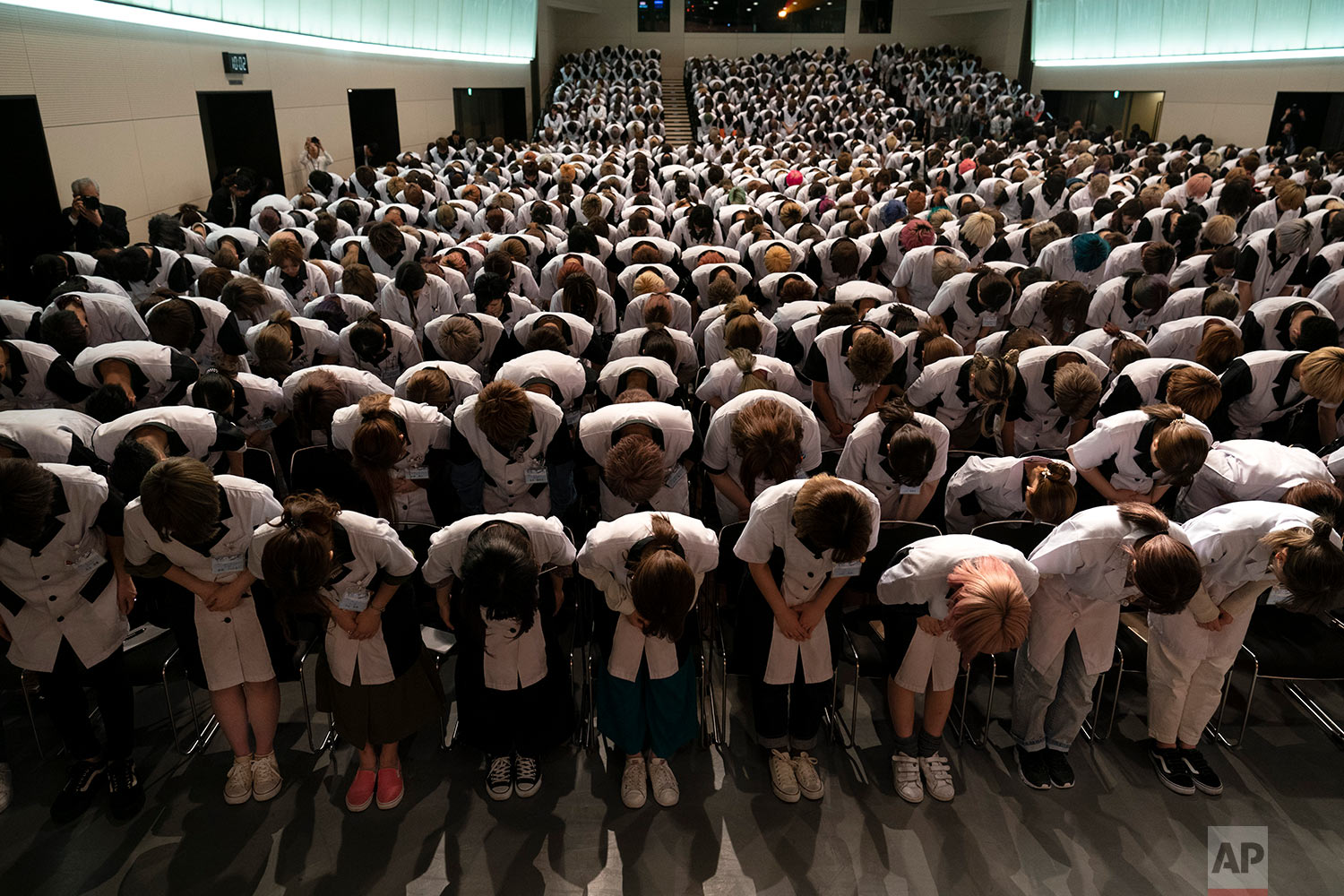Wearing school uniforms, students at Yamano Beauty College bow to a speaker during a ceremony held to celebrate the school's 83rd year anniversary in Tokyo, May 31, 2019. More than 1200 students from all over Japan are attending the school to be hair stylists or makeup artists. (AP Photo/Jae C. Hong)