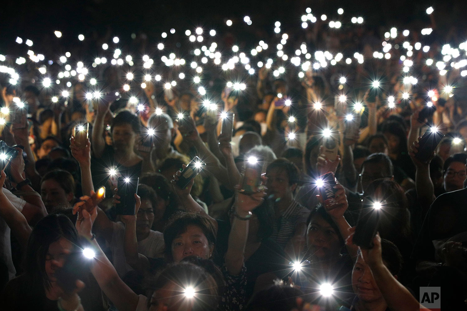 Attendees hold up their lit mobile phones during a rally by mothers in support of student protesters in Hong Kong, July 5, 2019. (AP Photo/Andy Wong)