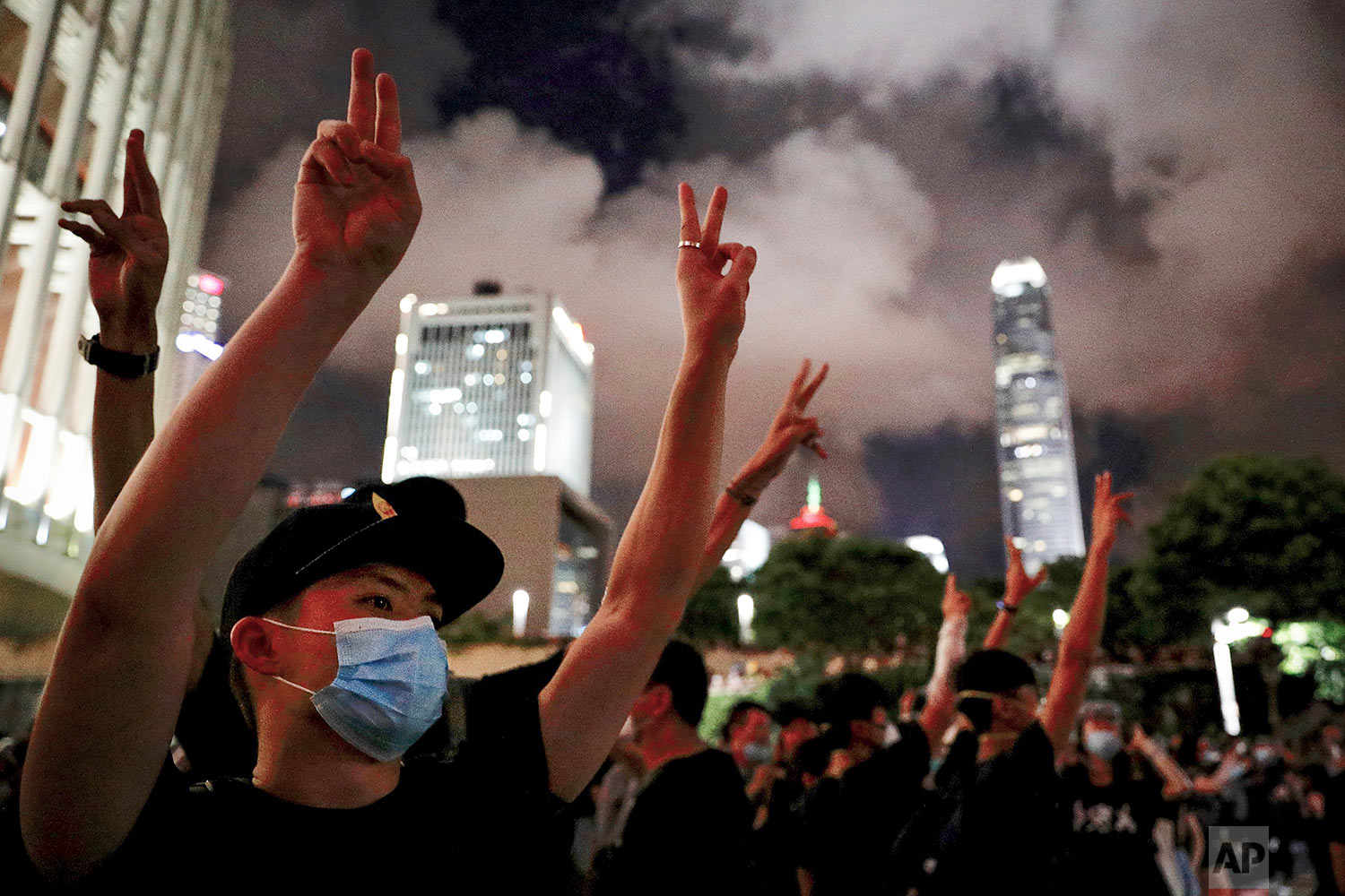 Protesters use hand signals to gestures for scissors during their attempt to break into the Legislative building in Hong Kong, July 1, 2019. (AP Photo/Vincent Yu)