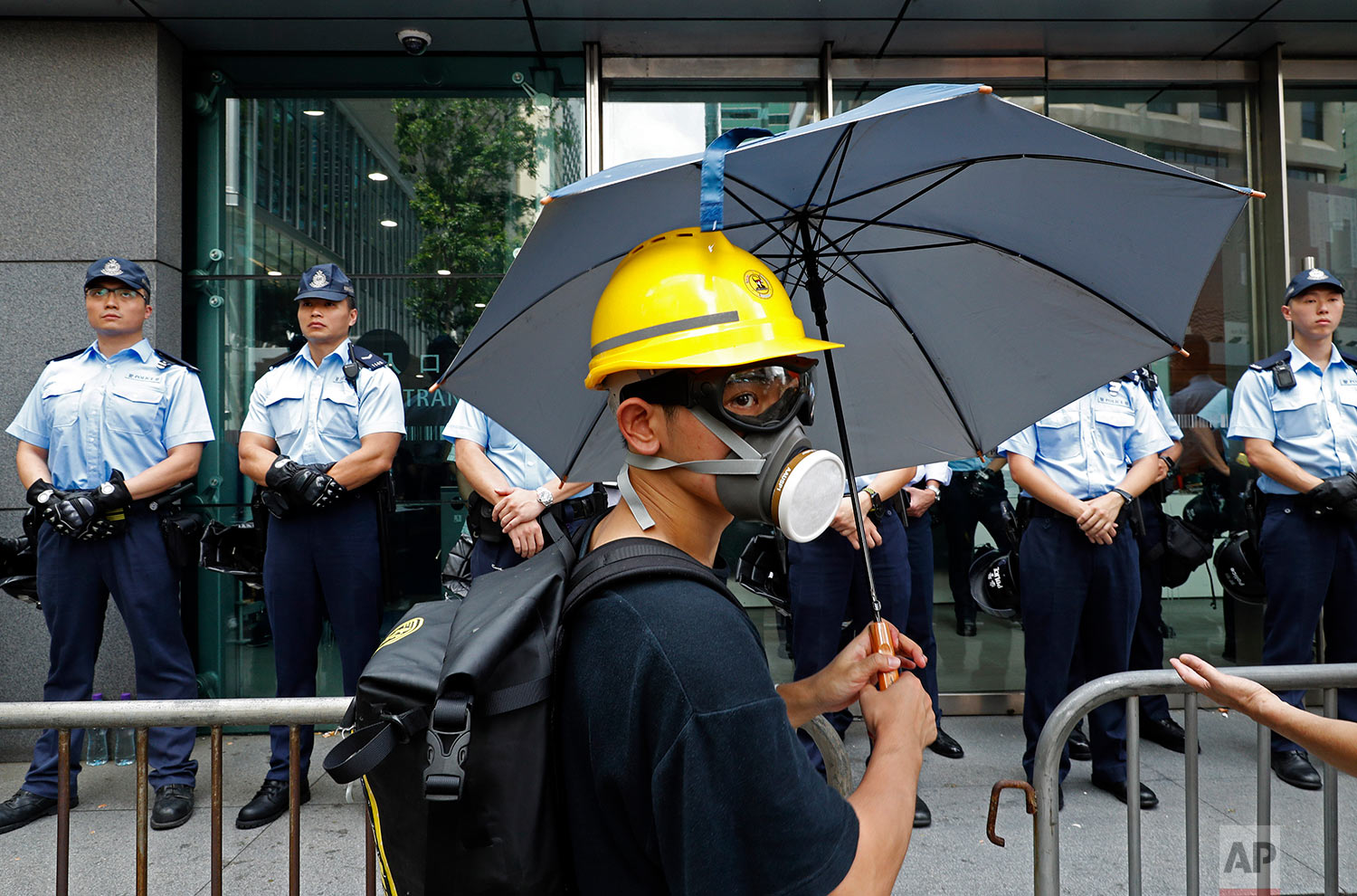A protestor stands in front of a line of policemen outside the police headquarters in Hong Kong on June 21, 2019. (AP Photo/Vincent Yu)