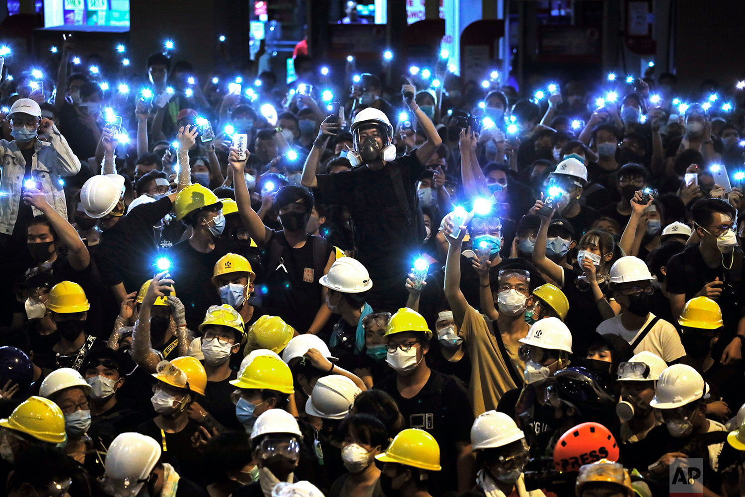 Protesters wearing yellow hardhats hold up mobile phone lights in front of police headquarters in Hong Kong, June 21, 2019. (AP Photo/Vincent Yu)