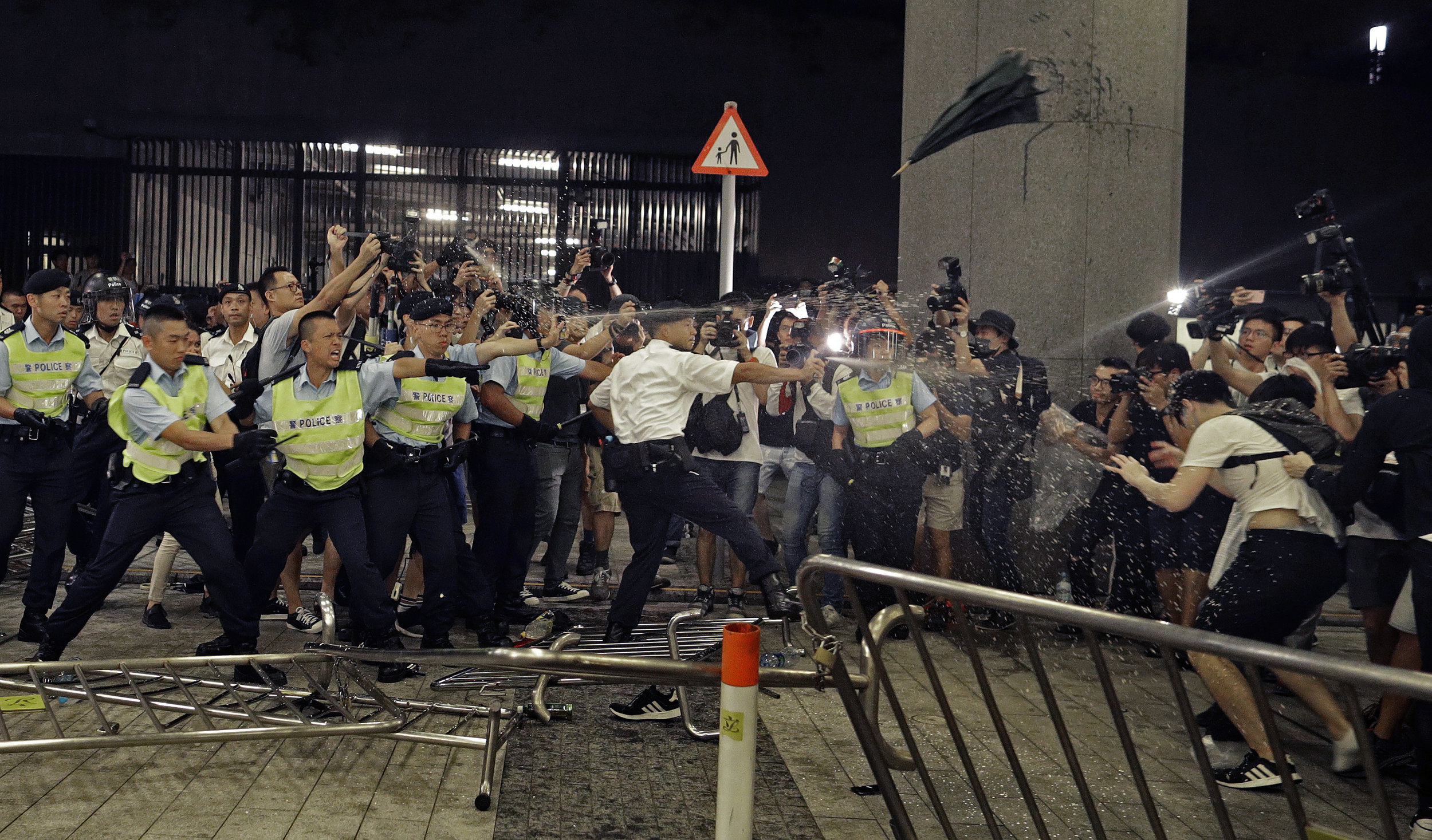 Police officers use pepper spray against protesters in a rally against the proposed amendments to the extradition law at the Legislative Council in Hong Kong on June 10, 2019. (AP Photo/Vincent Yu)