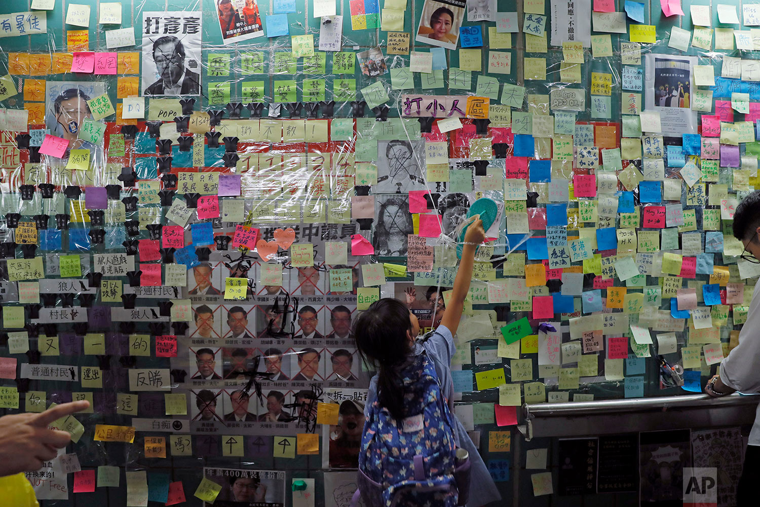A child reaches out to post-it notes on the city's version of the Lennon Wall in Hong Kong, July 12, 2019. (AP Photo/Kin Cheung)
