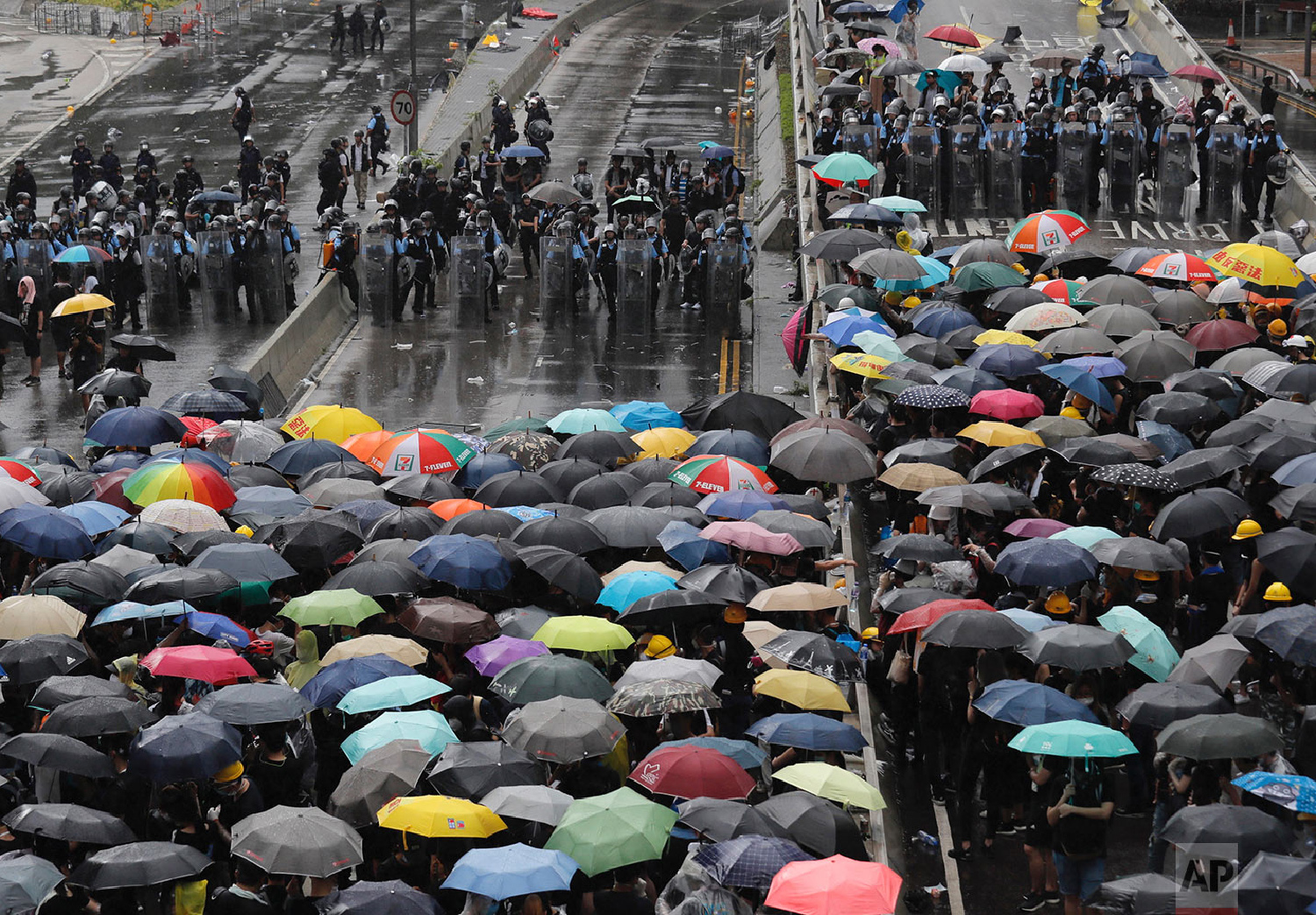 Protesters holding umbrellas face off police officers in anti-riot gear in Hong Kong, July 1, 2019. (AP Photo/Kin Cheung)