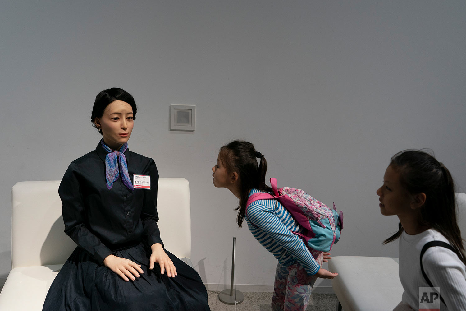 A young girl visiting from Singapore takes a closer look at a humanoid robot named Otonaroid at the National Museum of Emerging Science and Innovation Miraikan in Tokyo, June 6, 2019. (AP Photo/Jae C. Hong)