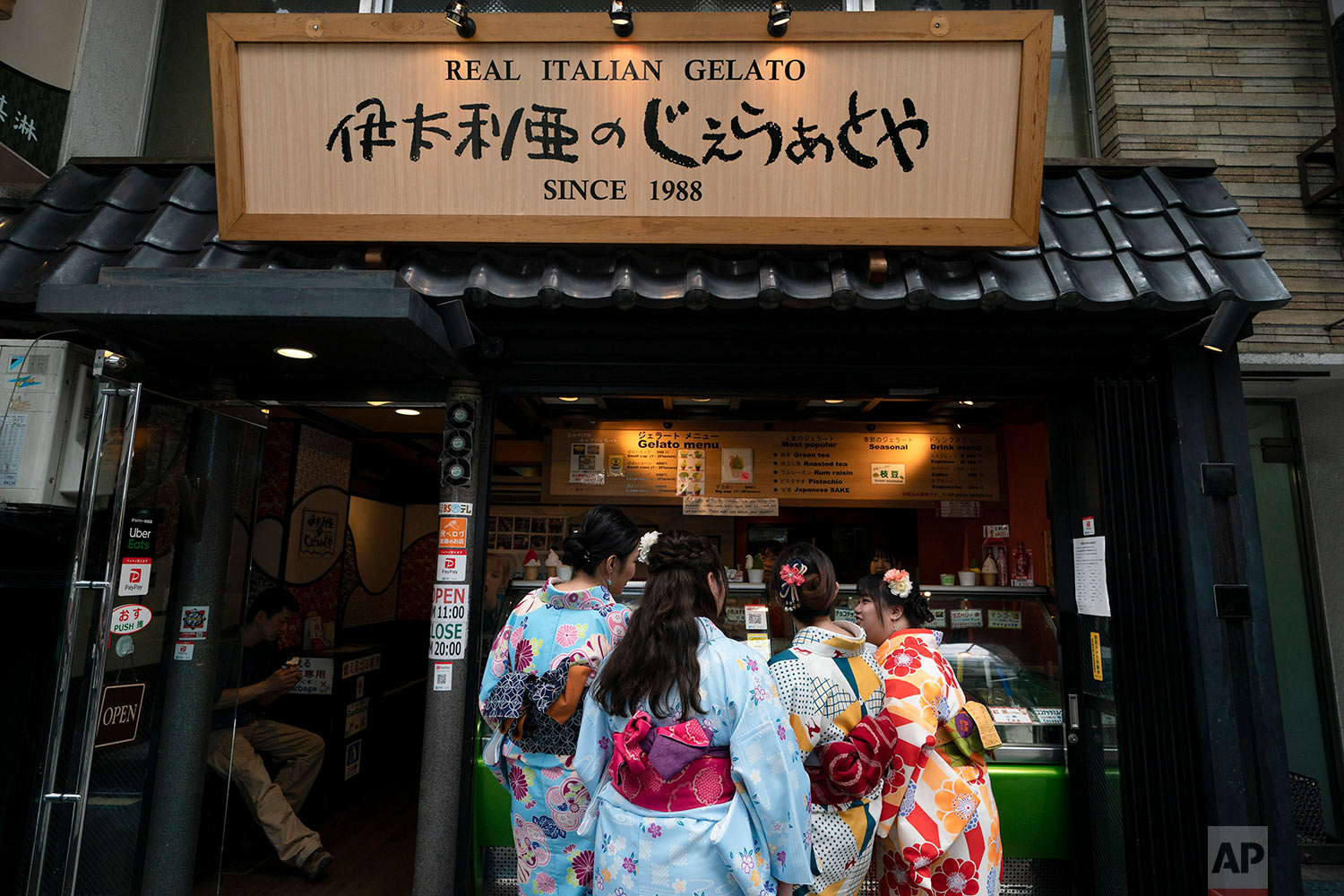 Wearing rental kimono, tourists visiting from Hong Kong order gelato after their visit to Sensoji Temple in the Taito district of Tokyo, June 3, 2019. (AP Photo/Jae C. Hong)