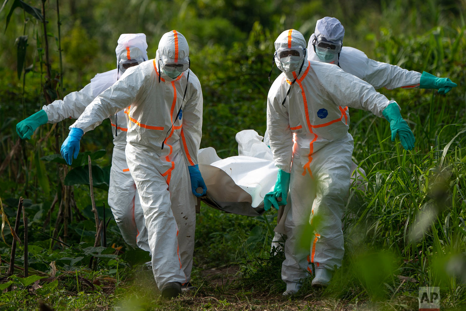 Burial workers dressed in protective gear carry the remains of Mussa Kathembo, an Islamic scholar who had prayed over those who were sick, and died of Ebola, in Beni, Congo, July 14, 2019. (AP Photo/Jerome Delay)