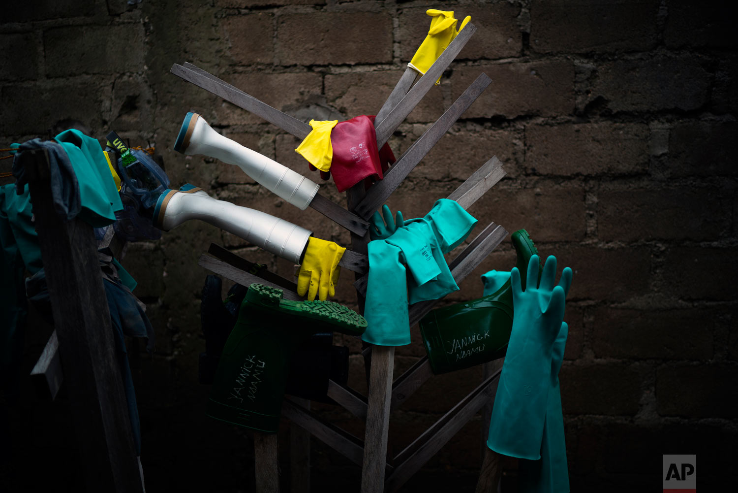 Rubber gloves and boots used by health workers treating Ebola patients hang to dry after being disinfected at an Ebola treatment center in Beni, Congo, July 12, 2019. (AP Photo/Jerome Delay)