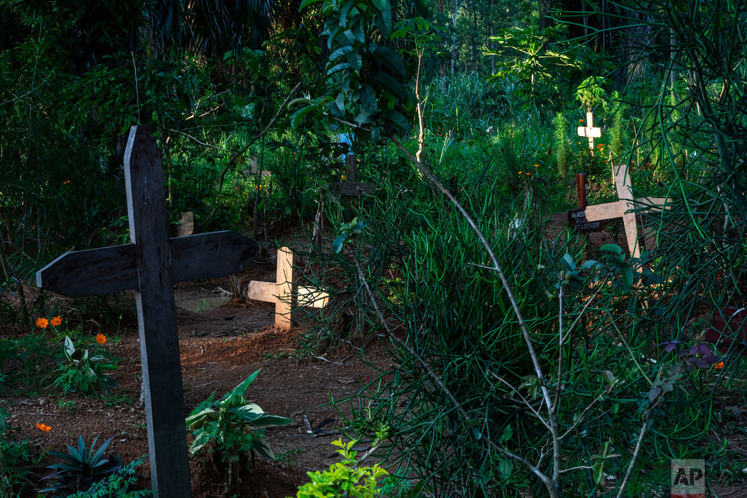 Light shines on freshly dug graves in Beni, Congo, July 16, 2019. (AP Photo/Jerome Delay)
