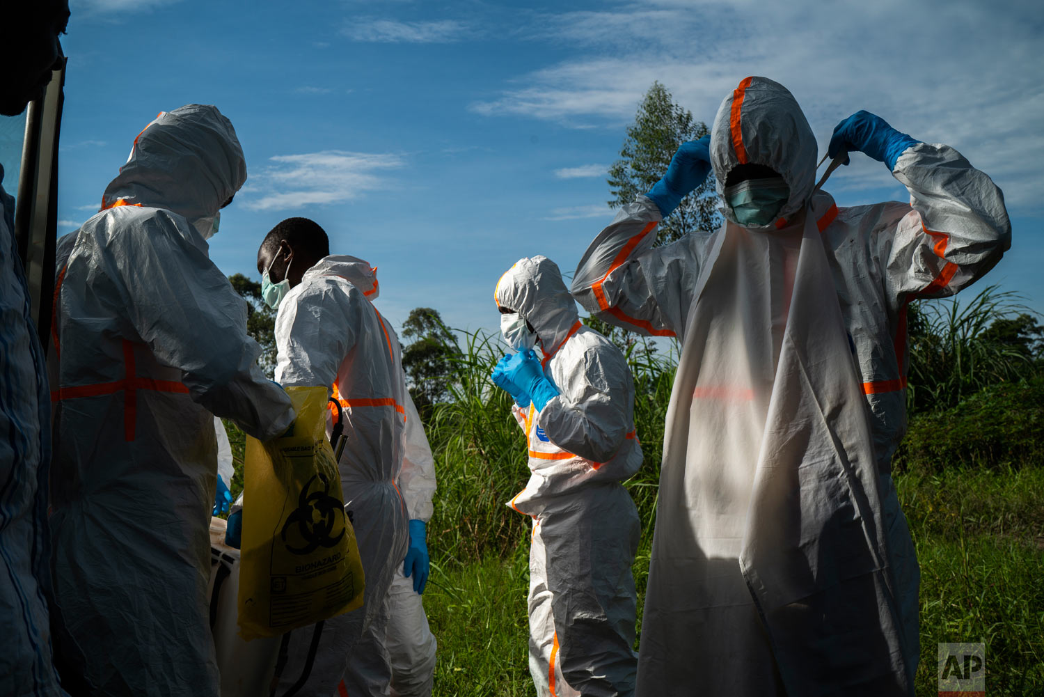Burial workers put on their protective gear before carrying the remains of Mussa Kathembo, an Islamic scholar who had prayed over those who were sick, and his wife Asiya to their final resting place in Beni, Congo, July 14, 2019. Both died of Ebola. (AP Photo/Jerome Delay)