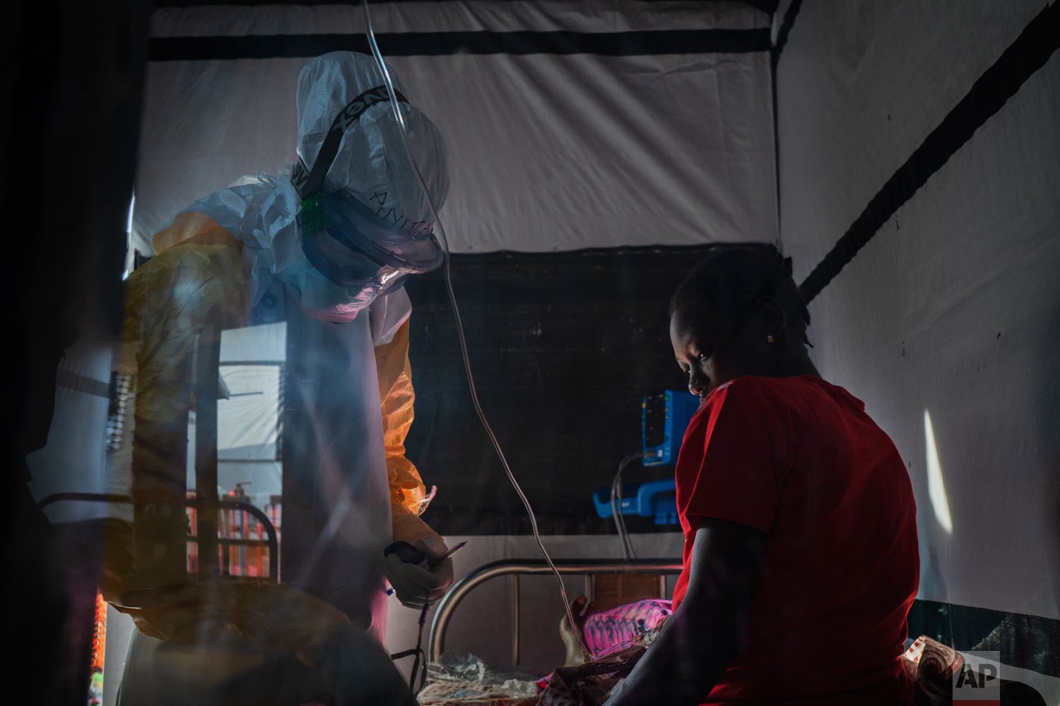 Health workers dressed in protective gear check on Ivette Adania, 24, a mother of four whose husband died of Ebola, at an Ebola treatment center in Beni, Congo, July 13 2019. (AP Photo/Jerome Delay)