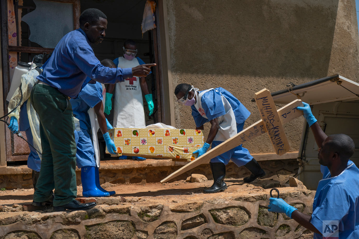 Red Cross workers carry the remains of 16-month-old Muhindo Kakinire from the morgue into a truck as health workers disinfect the area in Beni, Congo, July 14, 2019. (AP Photo/Jerome Delay)