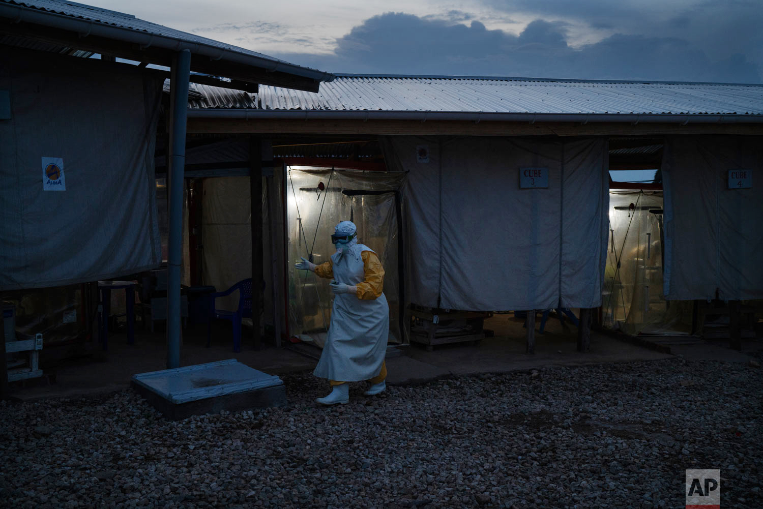 A health workers wearing protective suit walks out an isolation cube where he visited a patient at an Ebola treatment center in Beni, Congo, July 13, 2019. (AP Photo/Jerome Delay)