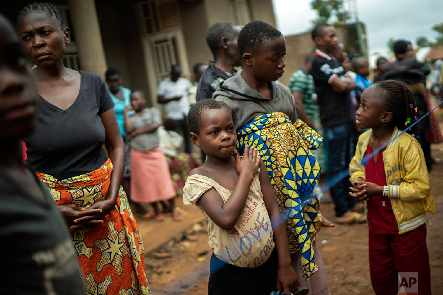 Relatives and neighbors of Mussa Kathembo an Islamic scholar who had prayed over those who were sick, and died of Ebola, wait to be vaccinated in Beni, Congo, July 13, 2019. (AP Photo/Jerome Delay)