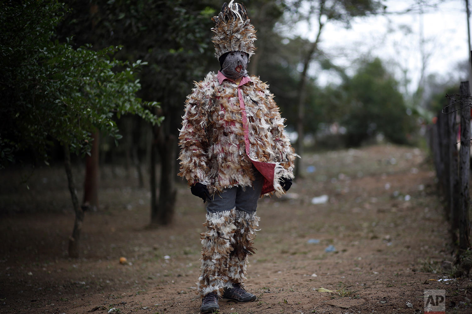 Maria Estela Pereira, mother of 11, poses in her feathered costume, in gratitude to St. Francis Solano, in Emboscada, Paraguay, Wednesday, July 24, 2019. (AP Photo/Jorge Saenz)