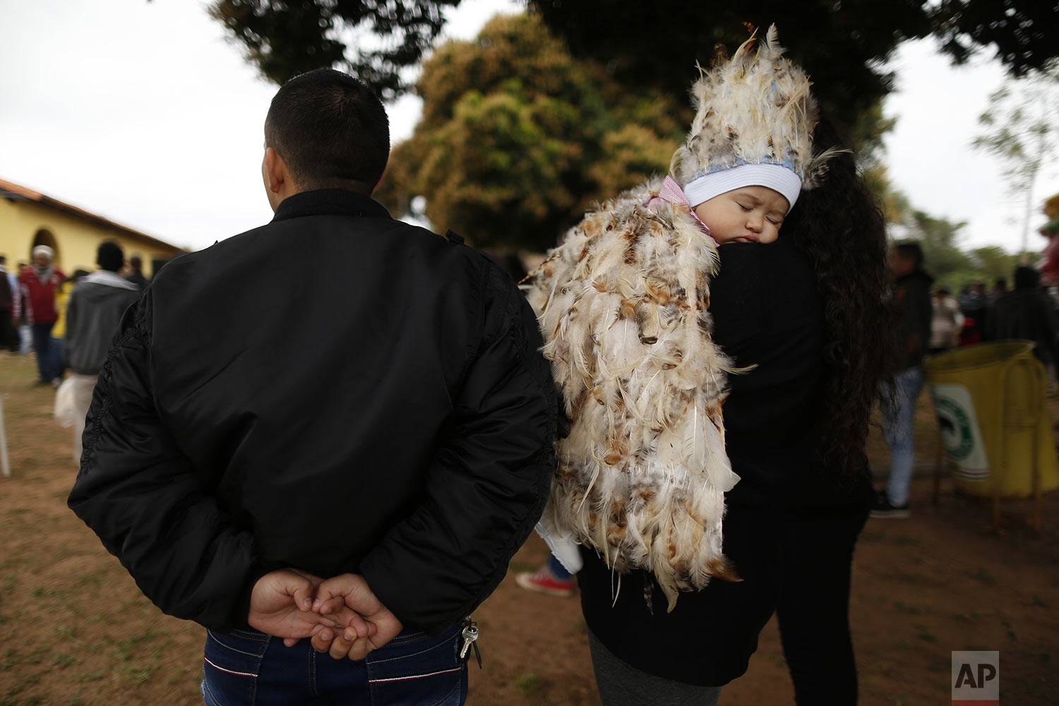 Jesus Cardozo Servin sleeps on his mother's shoulder dressed in a feathered costume during a Mass in honor of St. Francis Solano in Emboscada, Paraguay, Wednesday, July 24, 2019. The 9-month-old, who was born premature, was brought to the service by his parents as a devotee to express their gratitude to St. Francis Solano. (AP Photo/Jorge Saenz)