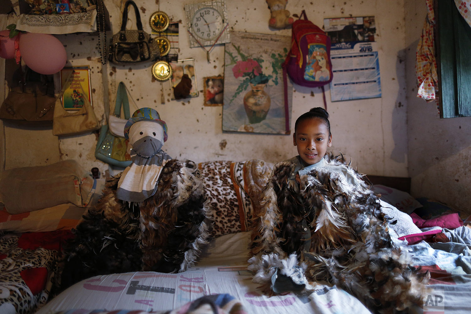 Alexis Aguero, left, and his sister Andrea sit in their bedroom dressed in their feathered costumes before they go to honor St. Francis Solano in Emboscada, Paraguay, Wednesday, July 24, 2019. (AP Photo/Jorge Saenz)