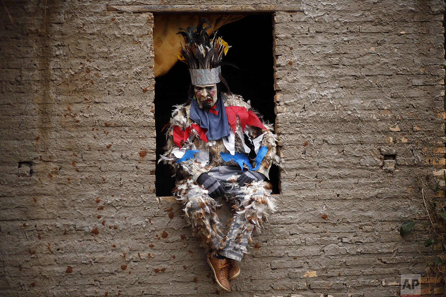 Farmer Genaro Servin sits on a window ledge in his feathered costume during the feast of St. Francis Solano in Emboscada, Paraguay, Wednesday, July 24, 2019. (AP Photo/Jorge Saenz)