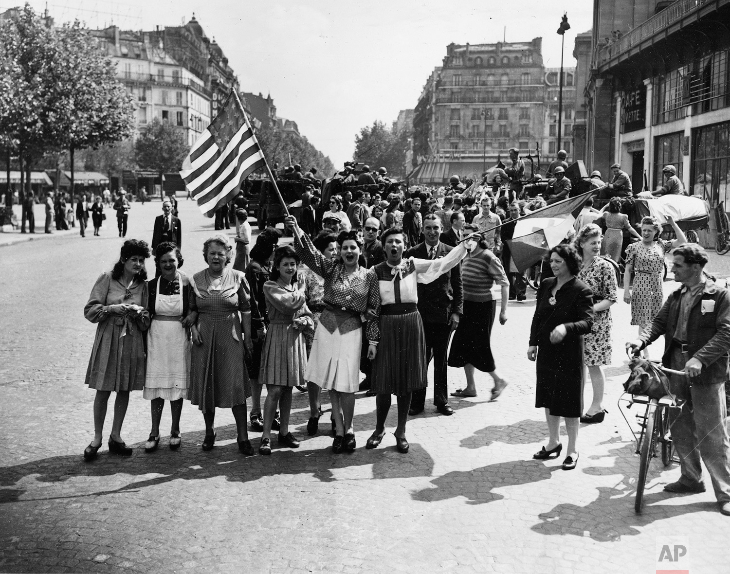 "French civilians with their hastily made American and French flags sing the ""Star Spangled Banner"" as they greet U.S. and Free French troops entering Paris, France, Aug. 25, 1944, after Allied liberation of the French capital from Nazi occupation in World War II. (AP Photo/Harry Harris)"