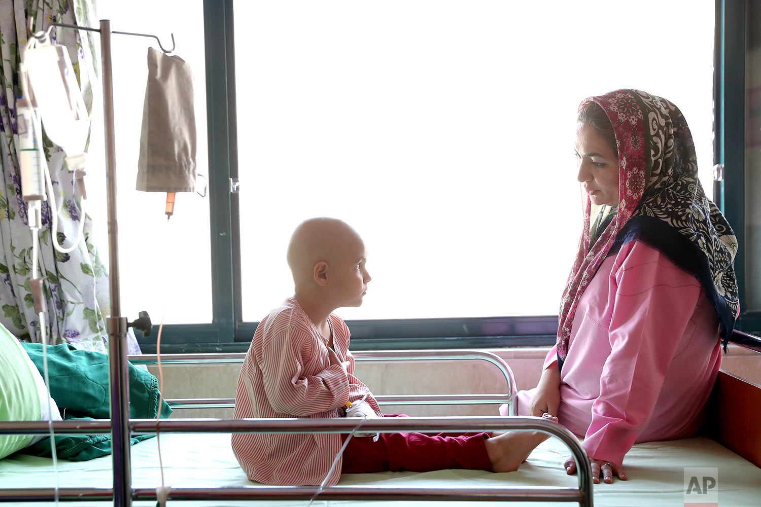 Parsa Amini, a 5-year-old boy suffering from eye cancer, speaks with his mother at Mahak Center's Hospital, in Tehran, Iran. (AP Photo/Ebrahim Noroozi)