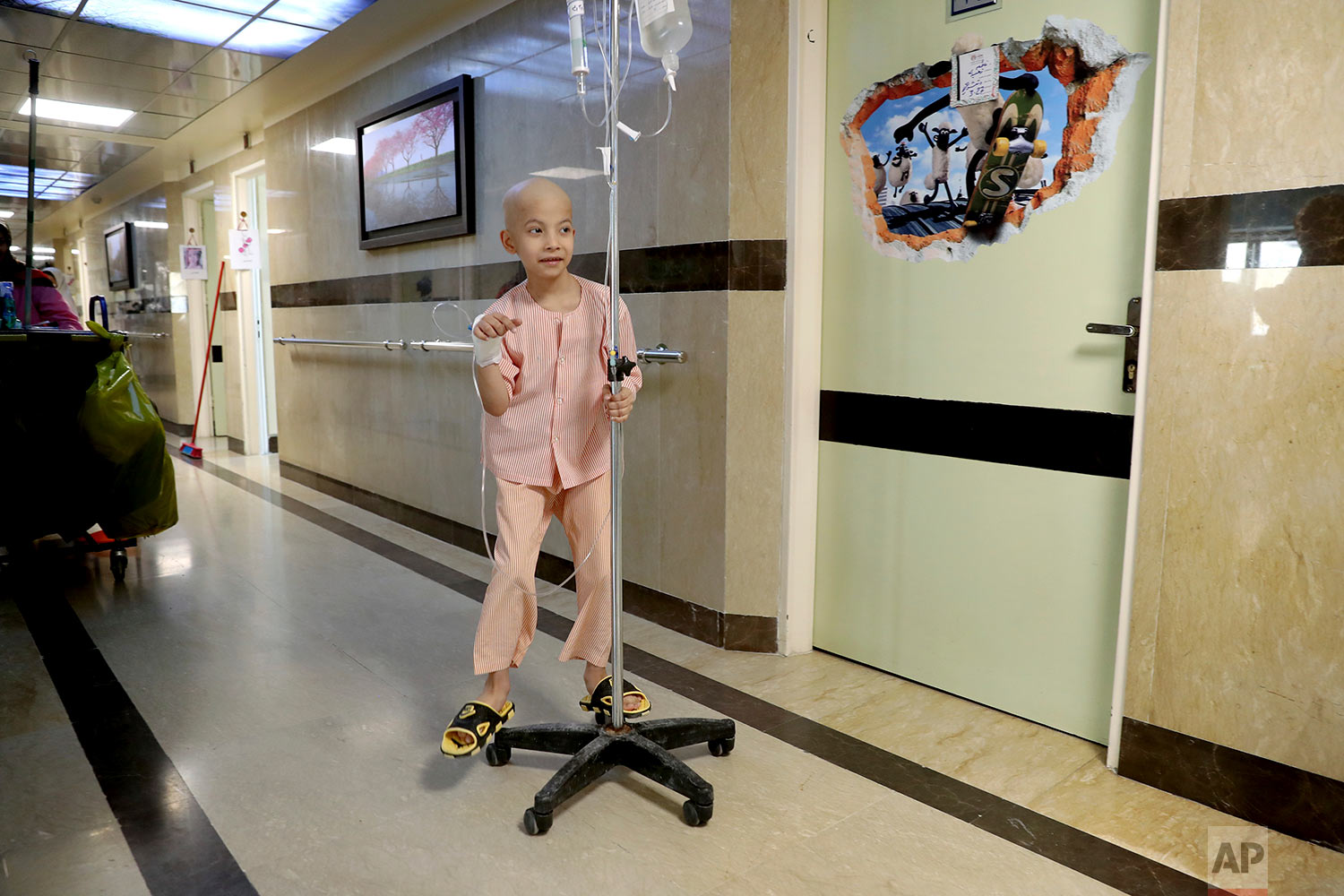 Taha Shakouri, an 8-year-old boy suffering from liver cancer, plays at Mahak Center's, Hospital in Tehran, Iran. (AP Photo/Ebrahim Noroozi)