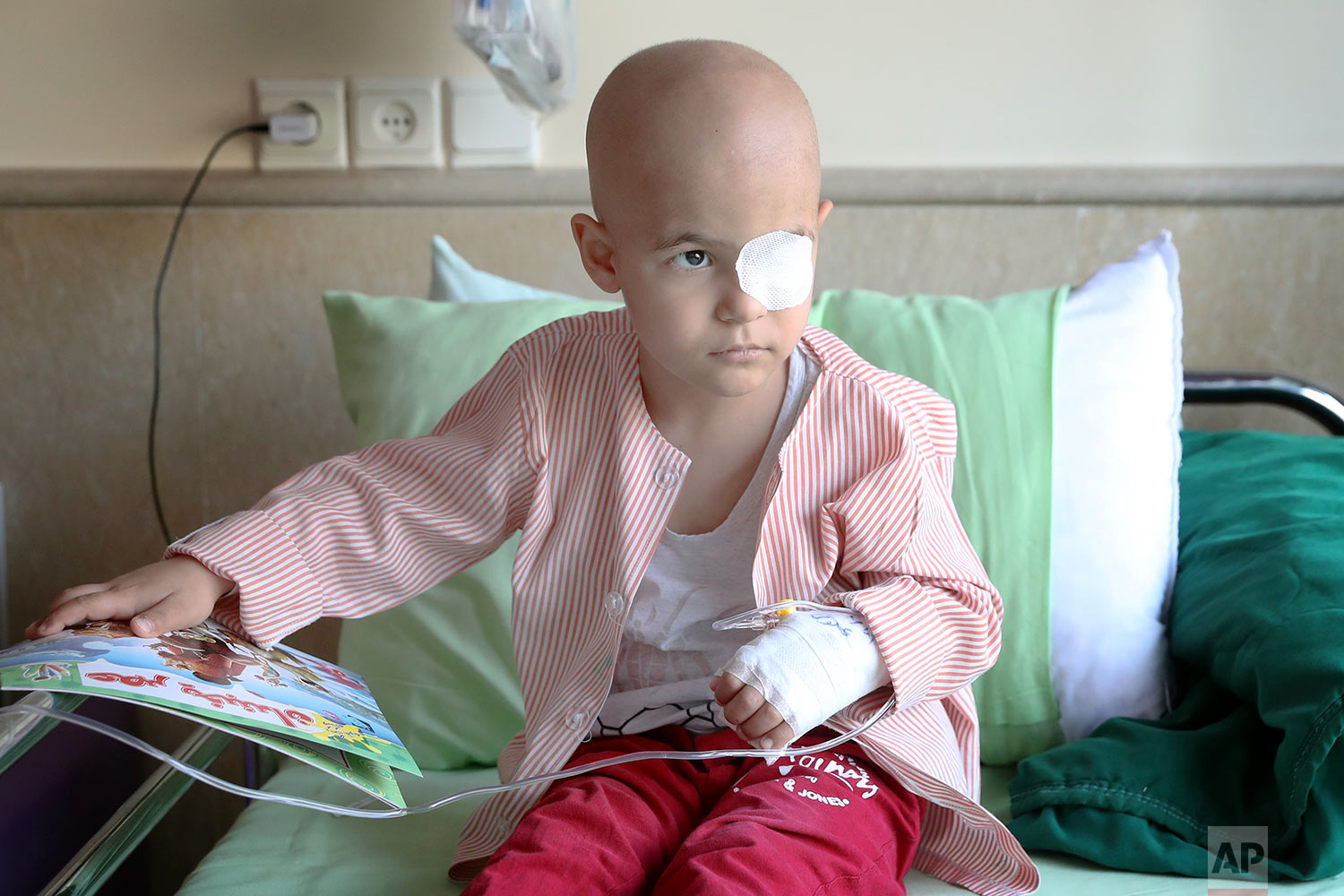 Parsa Amini, a 5-year-old boy suffering from eye cancer, sits on his bed at Mahak Children's Hospital, in Tehran, Iran. (AP Photo/Ebrahim Noroozi)