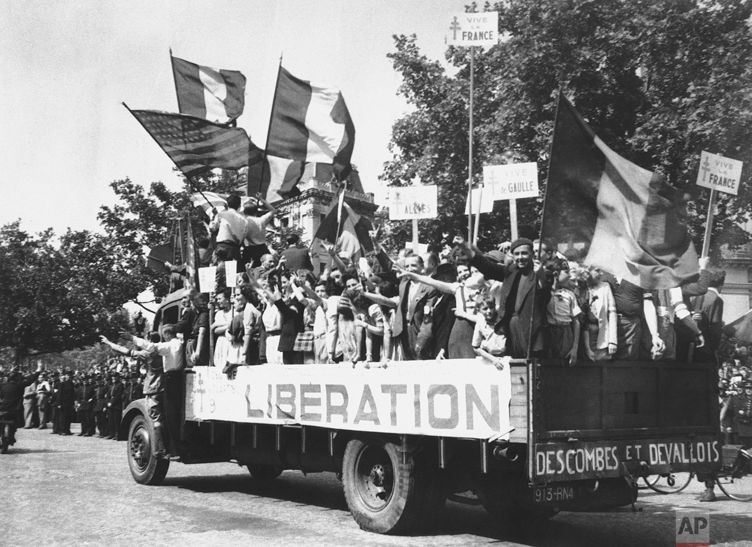 A truck load of Parisians waving flags and carrying Vive De Gaulle banners drives through the streets of a madly rejoicing Paris, on August 28, 1944. (AP Photo/Peter Carroll)
