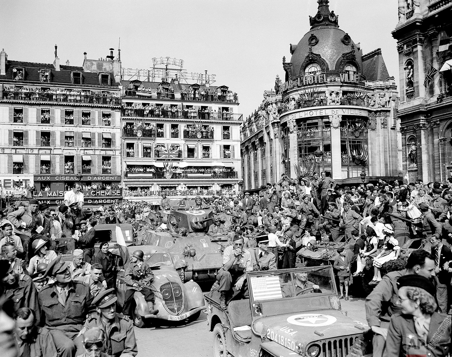 Thousands of Parisians jam the Place de l'Hotel de Ville (City Hall) in the French capital, Aug. 26, 1944, to watch the big parade for Gen. Charles de Gaulle. Other civilians peer from windows and balconies. Allied flags are displayed throughout the square. Part of the City Hall is visible at extreme right. (AP Photo/Wartime Picture Pool/Peter J. Carroll)