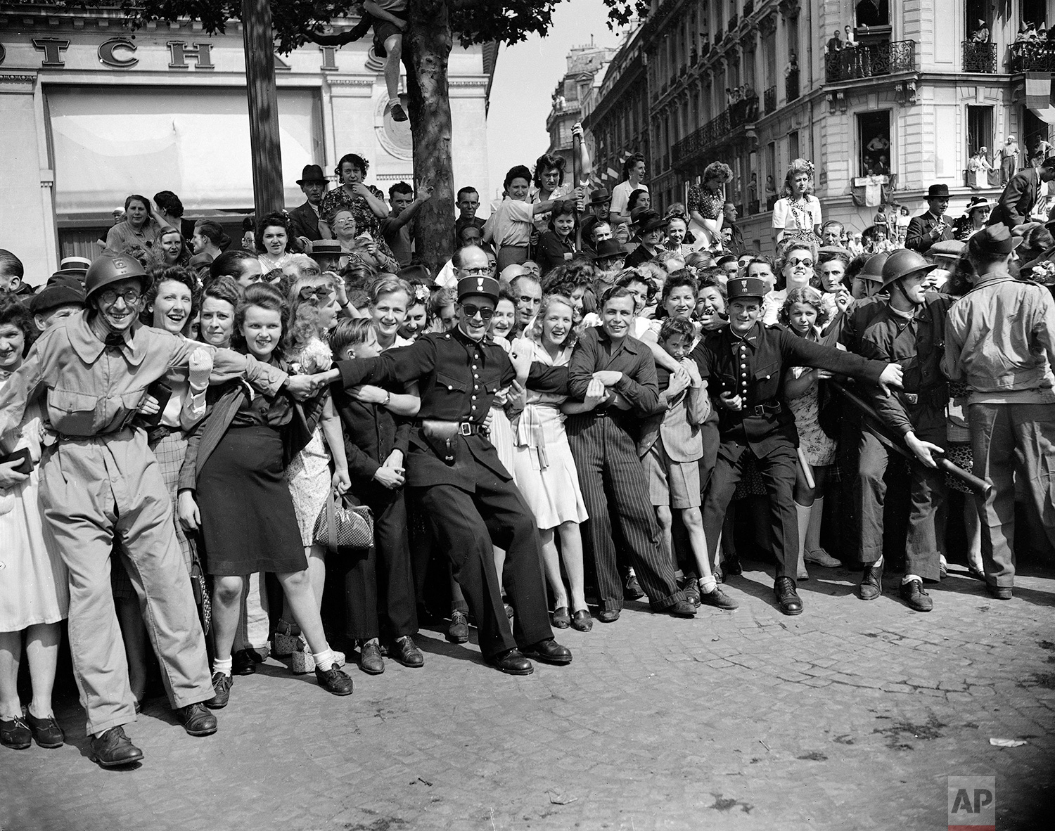 Gendarmes and F.F.I. seem to enjoy the task of holding back crowds of people as they throng the streets to see General Charles De Gaulle, Aug. 26, 1944. (AP Photo/Laurence Harris)