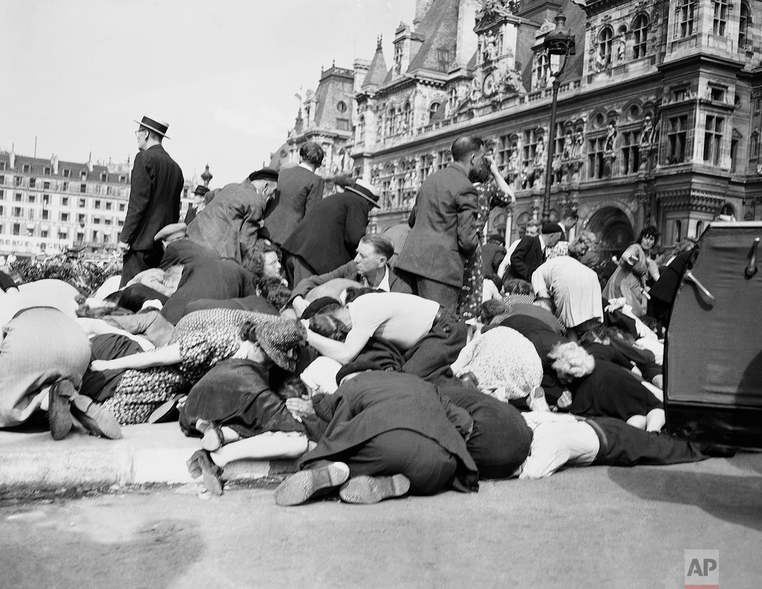 Parisians drop to the ground to duck sniper bullets, as firing starts at the Place de L'Hotel de Ville, in Paris, during liberation celebrations on August 26, 1944. City hall is in background, right. (AP Photo/Peter J. Carroll)