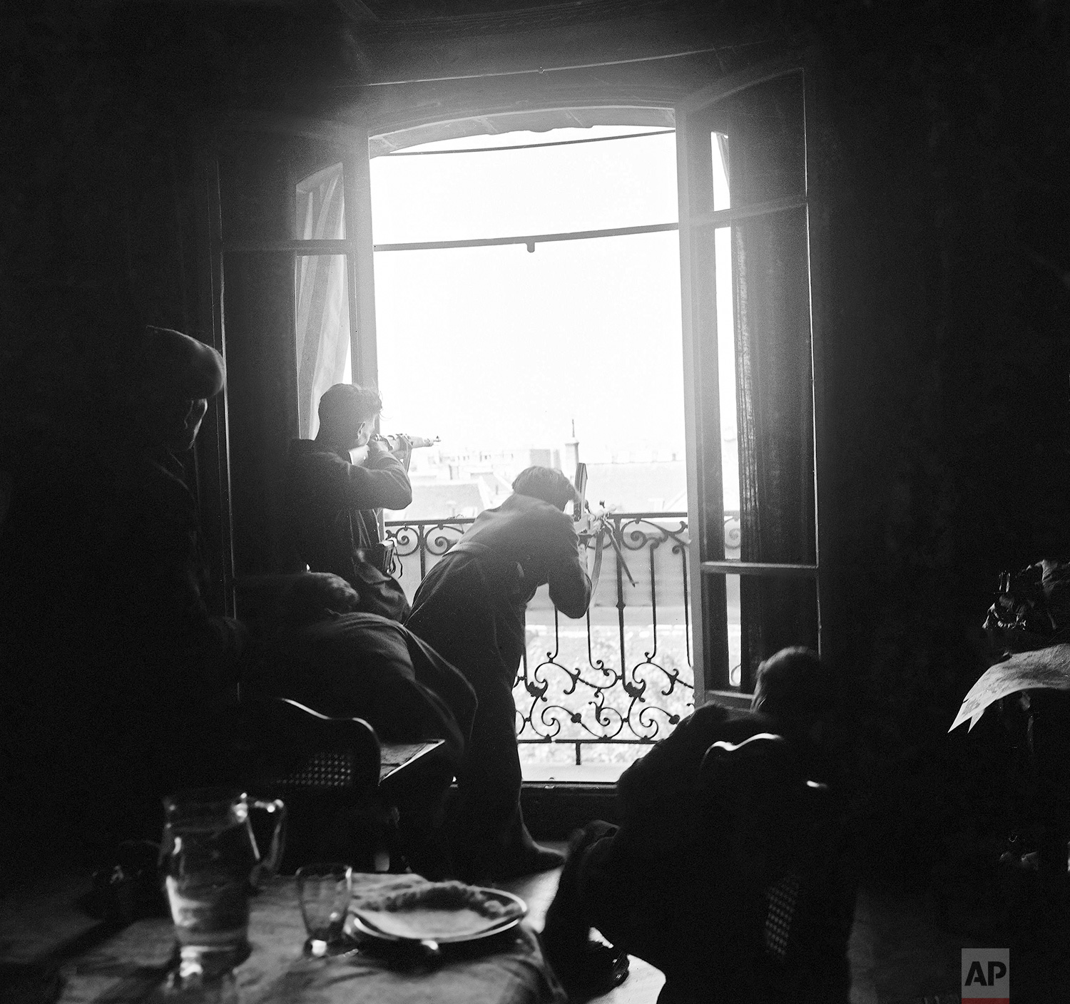Members of the French Forces of the Interior (FFI) shoot at German snipers from a window in Paris on August 26, 1944. (AP Photo/Peter J. Carroll)