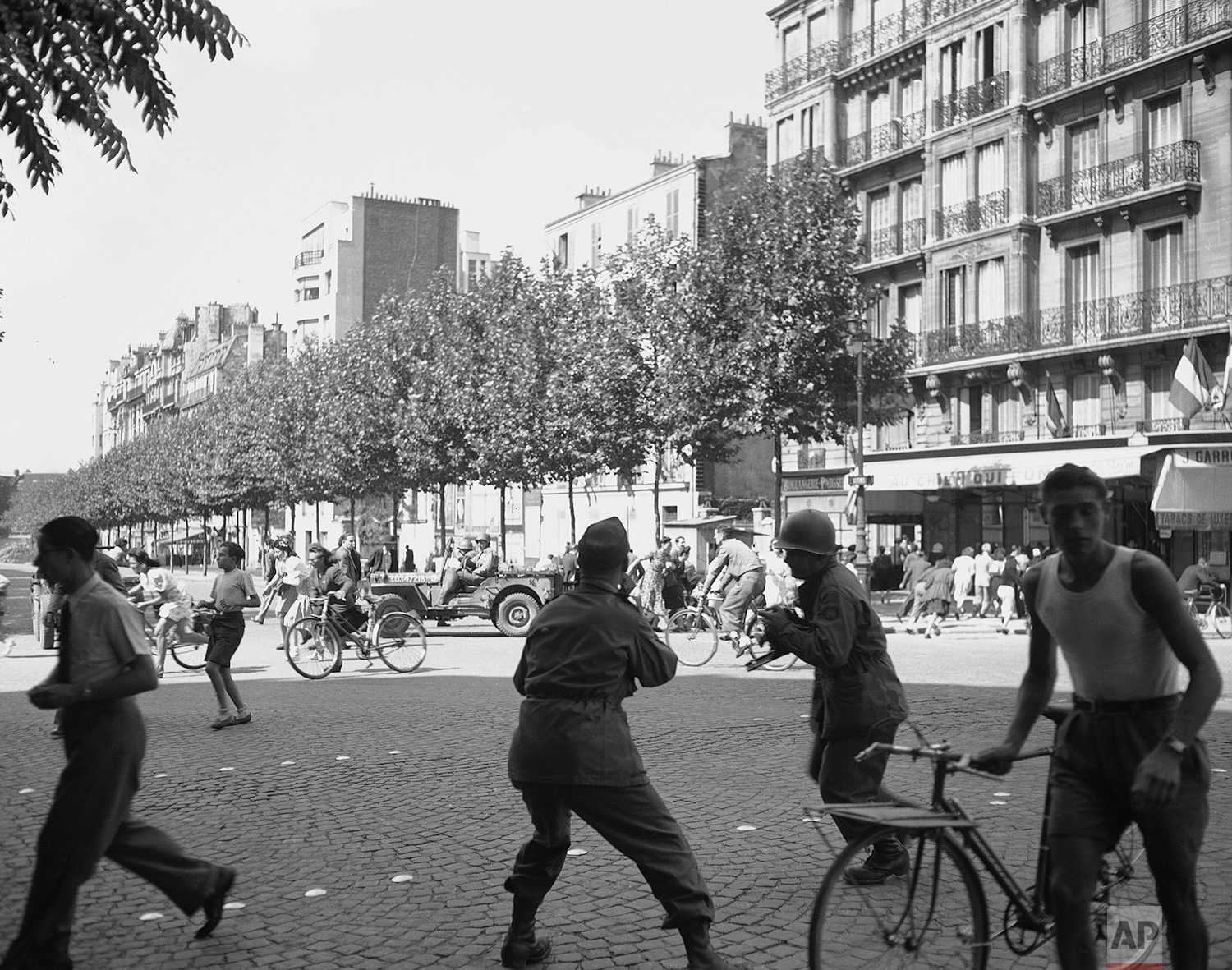 Crowds in a street run for shelter to get out of the line of German sniper fire in Paris on August 29, 1944. In foreground are two war photographers shooting this dramatic scene. (AP Photo/Peter J. Carroll)