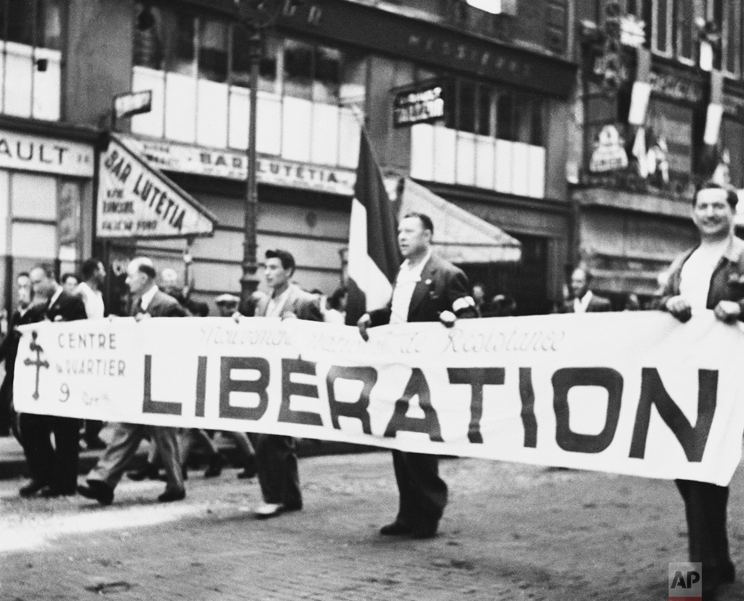 Carrying a huge banner proclaiming the liberation of Paris, men of the Maqui march through the city's streets in Paris on August 28, 1944. Their jubilitation was a bit hasty, however, for peace has not yet come to liberated Paris. Mopping up of snipers continues, with the job of restoring order in the French capital left to General De Gaulle. (AP Photo)