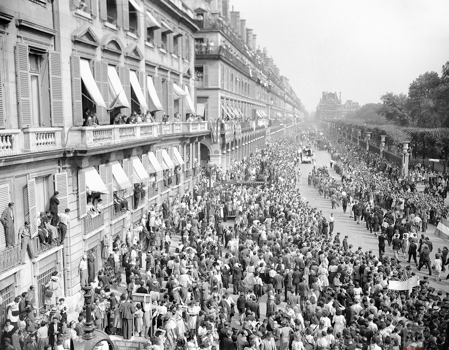 Through streets lined with madly cheering Parisians, General Charles de Gaulle made his parade from the Arc de Triomphe to the Place de La Concorde on August 27, 1944. From every building flew the tricolor flag, the Union Jack, and the Stars and Stripes. (AP Photo/Harry Harris)