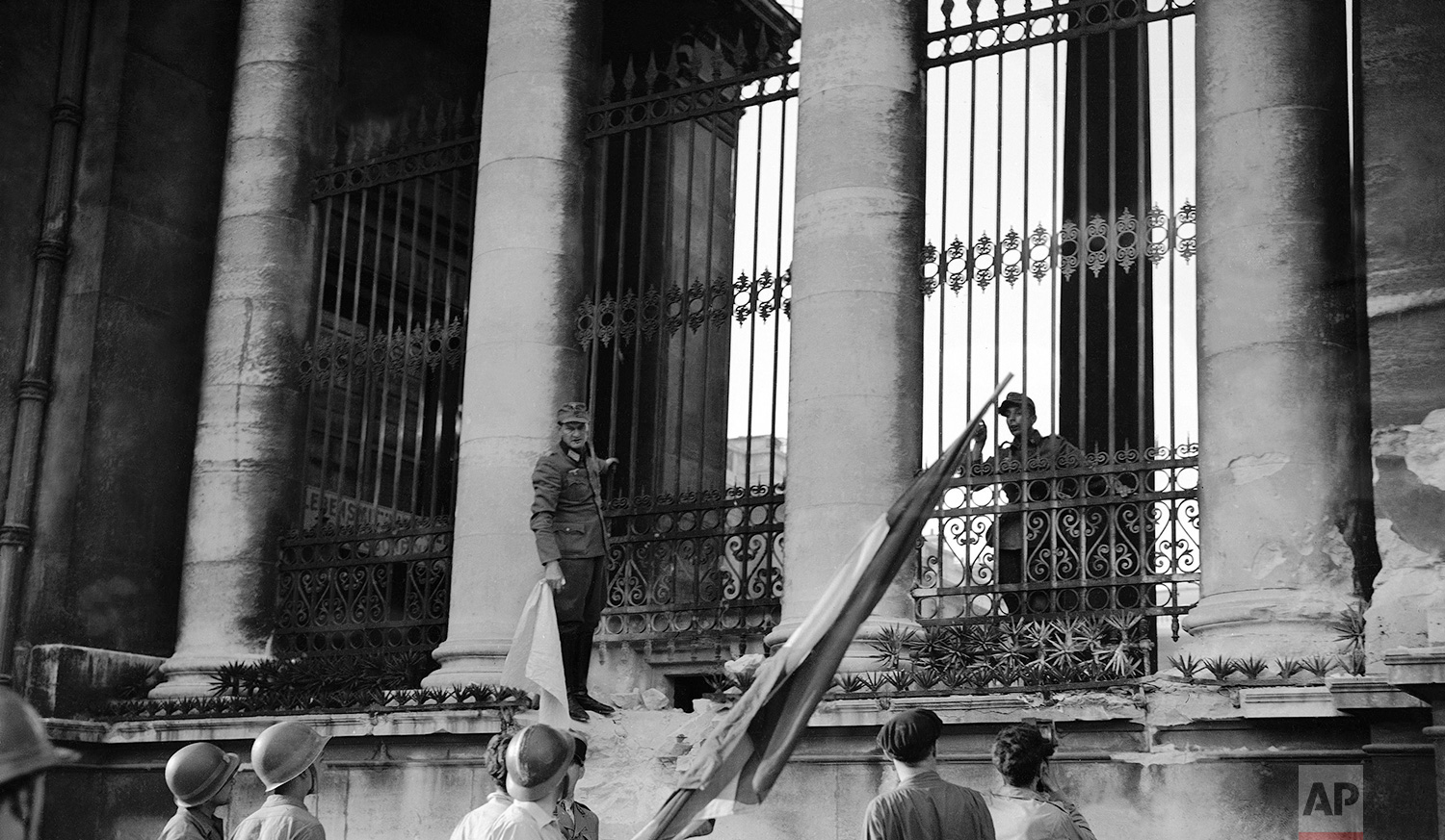 A German officer standing beside one of the columns of the Chamber of Deputies building, in Paris, France on August 30, 1944, holds white flag of truce as he negotiates surrender of German forces within the building with a French soldier carrying the Tricolor. Frenchman waits to hoist flag over the building, where one of the last armed clashes took place before the capital was cleared of the Germans. (AP Photo/Harry Harris)