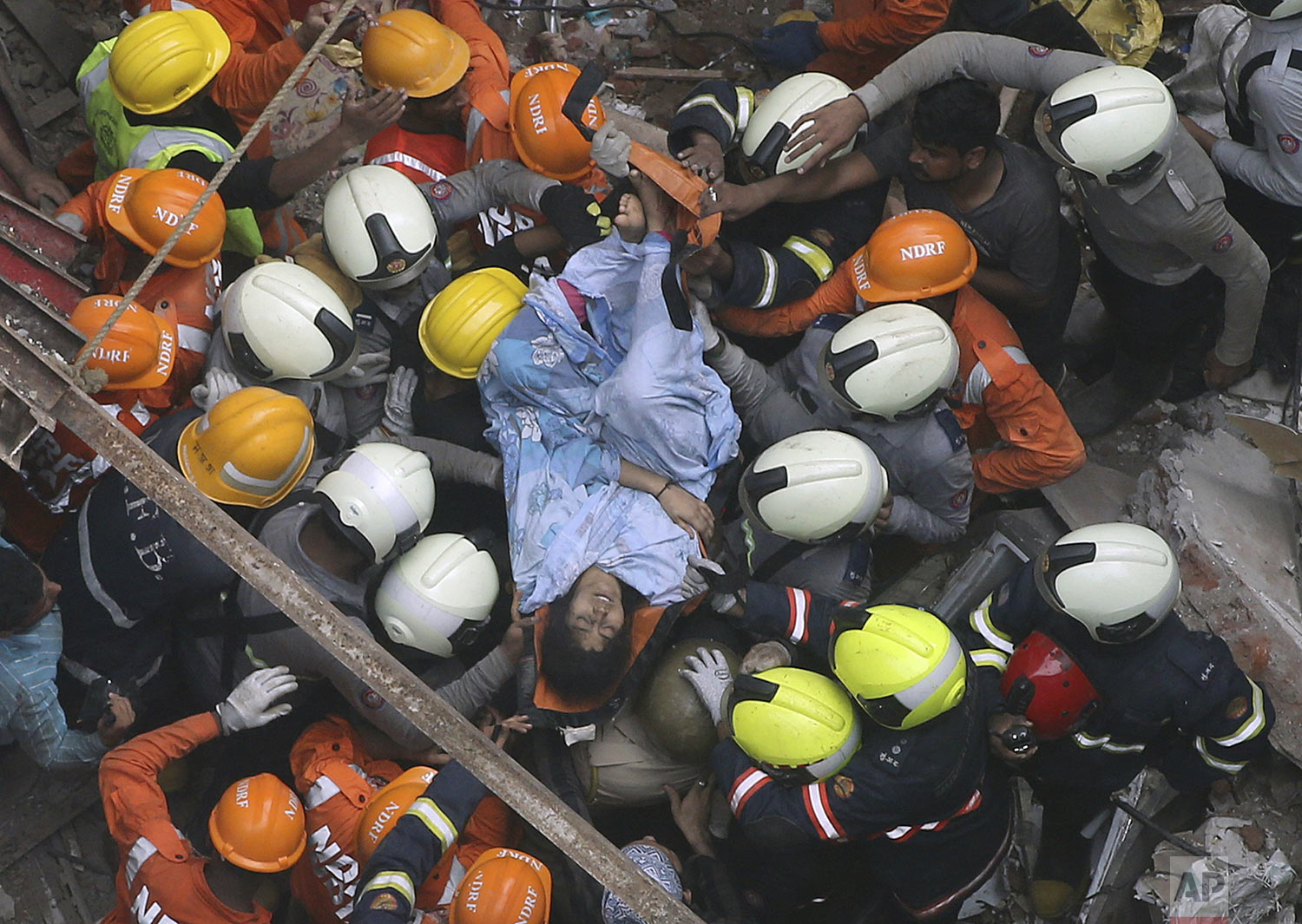 Rescuers carry out a survivor from the site of a building that collapsed in Mumbai, India, Tuesday, July 16, 2019.  (AP Photo/Rajanish Kakade)