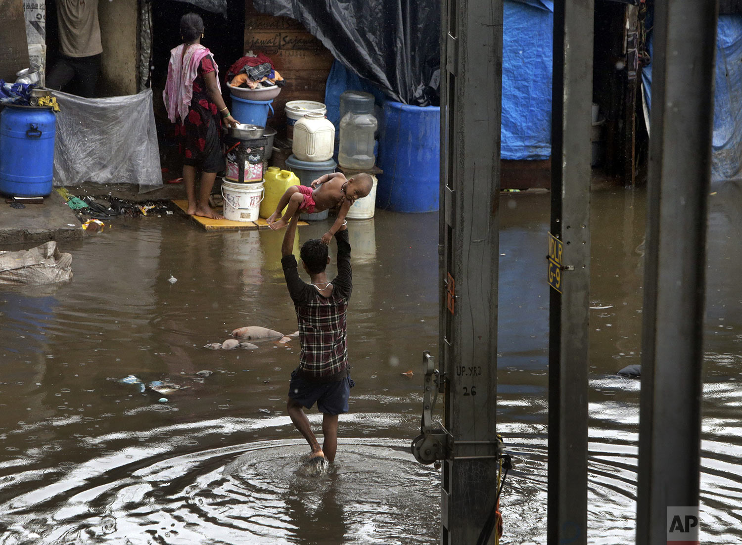 A man holds a child high above his head as he wades through a waterlogged street following heavy rains in Mumbai, India, July 2, 2019. (AP Photo/Rajanish Kakade)
