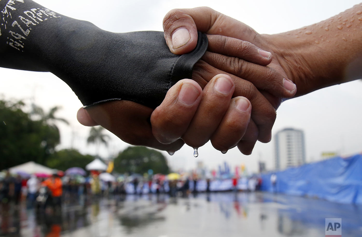 Protesters link hands as they lead a march under the rain towards the Philippine Congress to protest the 4th State of the Nation (SONA) address by President Rodrigo Duterte in suburban Quezon city, northeast of Manila, Philippines, July 22, 2019. (AP Photo/Bullit Marquez)