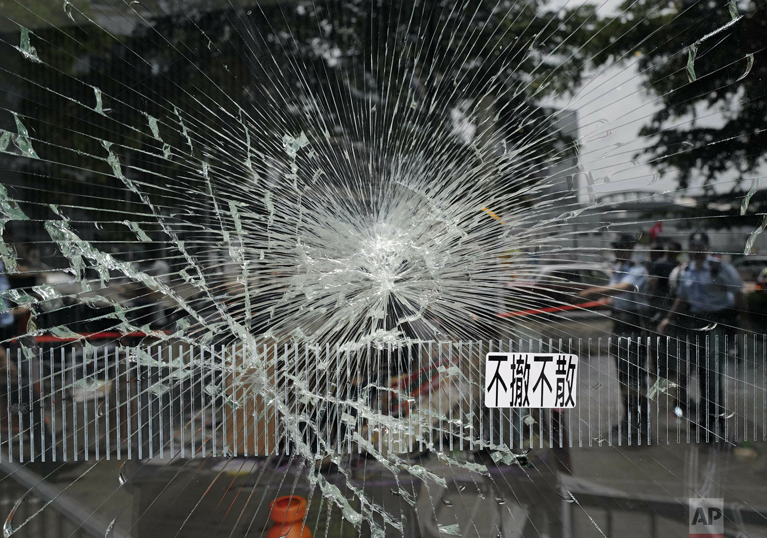 Police officers stand guard near  broken glass outside the Legislative Council building in Hong Kong, July 2, 2019.  (AP Photo/Vincent Yu)