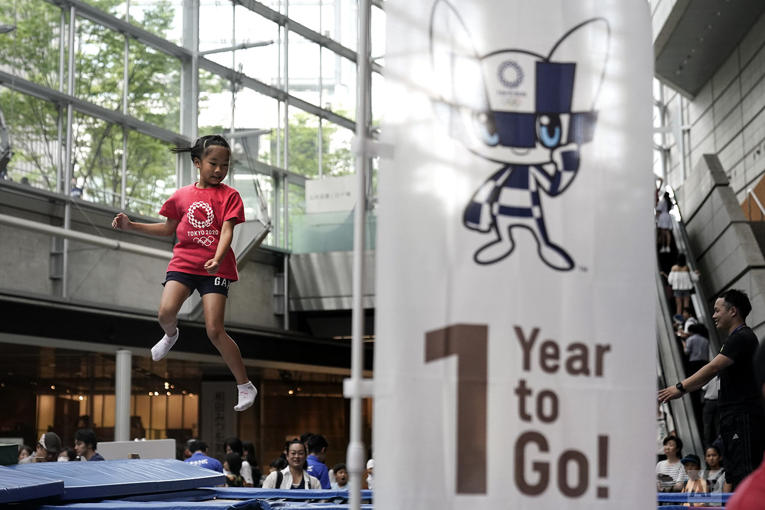 A girl plays on a trampoline during a One Year to Go ceremony held at Tokyo International Forum to mark one year until the opening of the Tokyo 2020 Olympics, in Tokyo, July 24, 2019, photo. (AP Photo/Jae C. Hong)